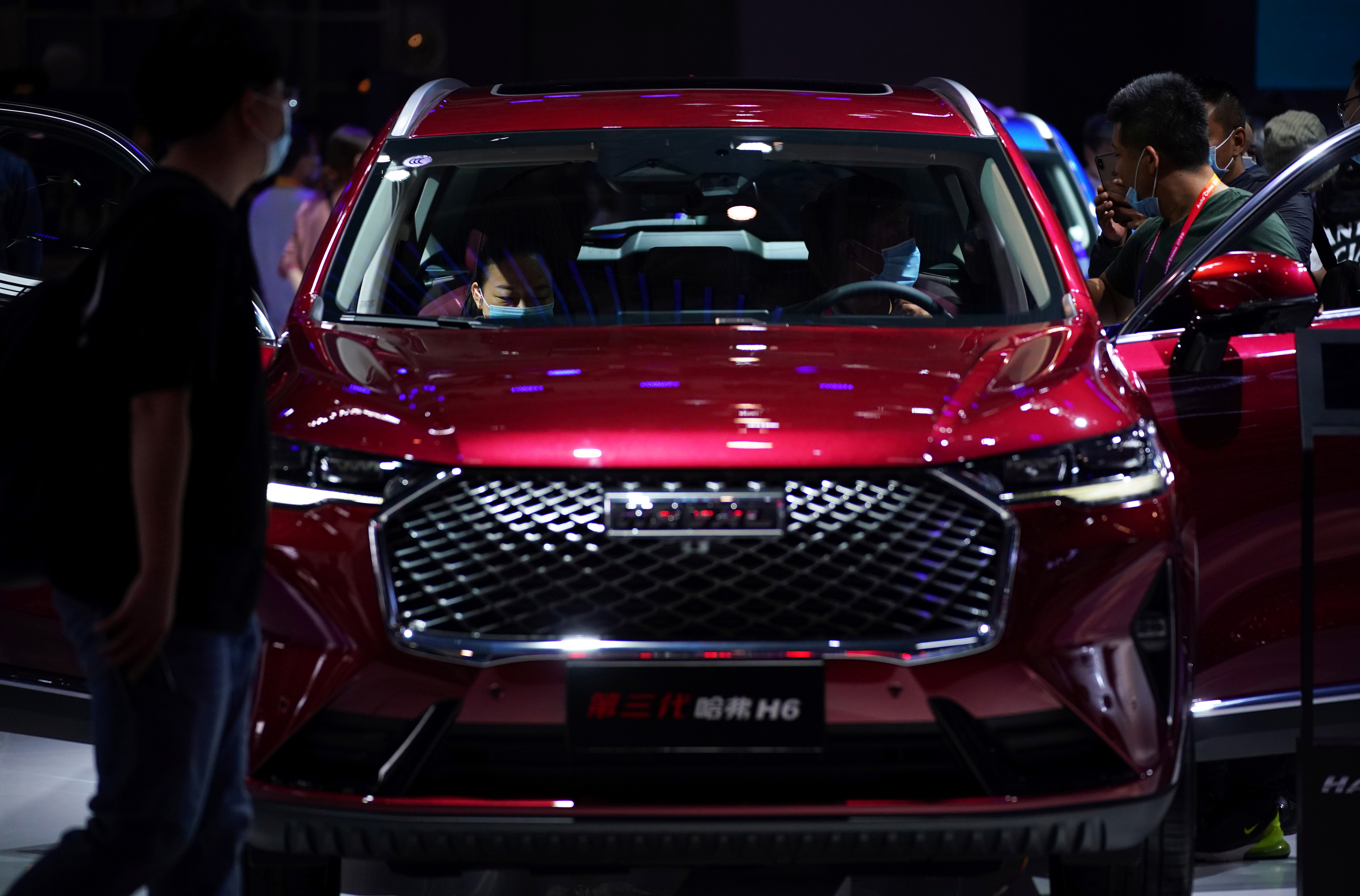 People wearing face masks check out the third-generation Haval H6 SUV by GWM (Great Wall Motors) at the Beijing International Automotive Exhibition, or Auto China show, following the coronavirus disease (COVID-19) outbreak, in Beijing, China September 27, 2020. REUTERS/Tingshu Wang