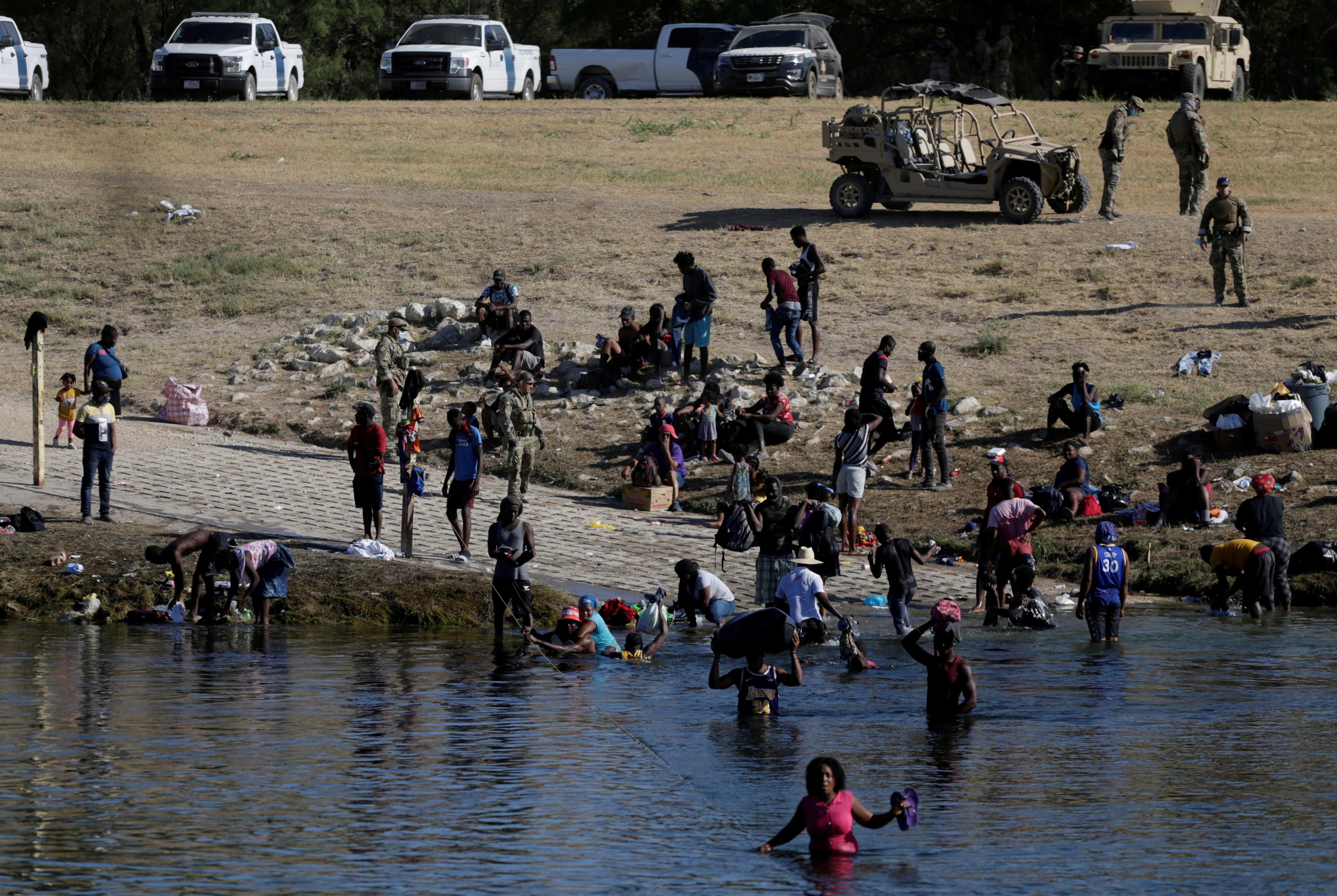 Migrants seeking refuge in the U.S. wade across the Rio Grande river from Del Rio, Texas, U.S. toward Ciudad Acuna, Mexico, in Ciudad Acuna, Mexico September 22, 2021. REUTERS/Daniel Becerril