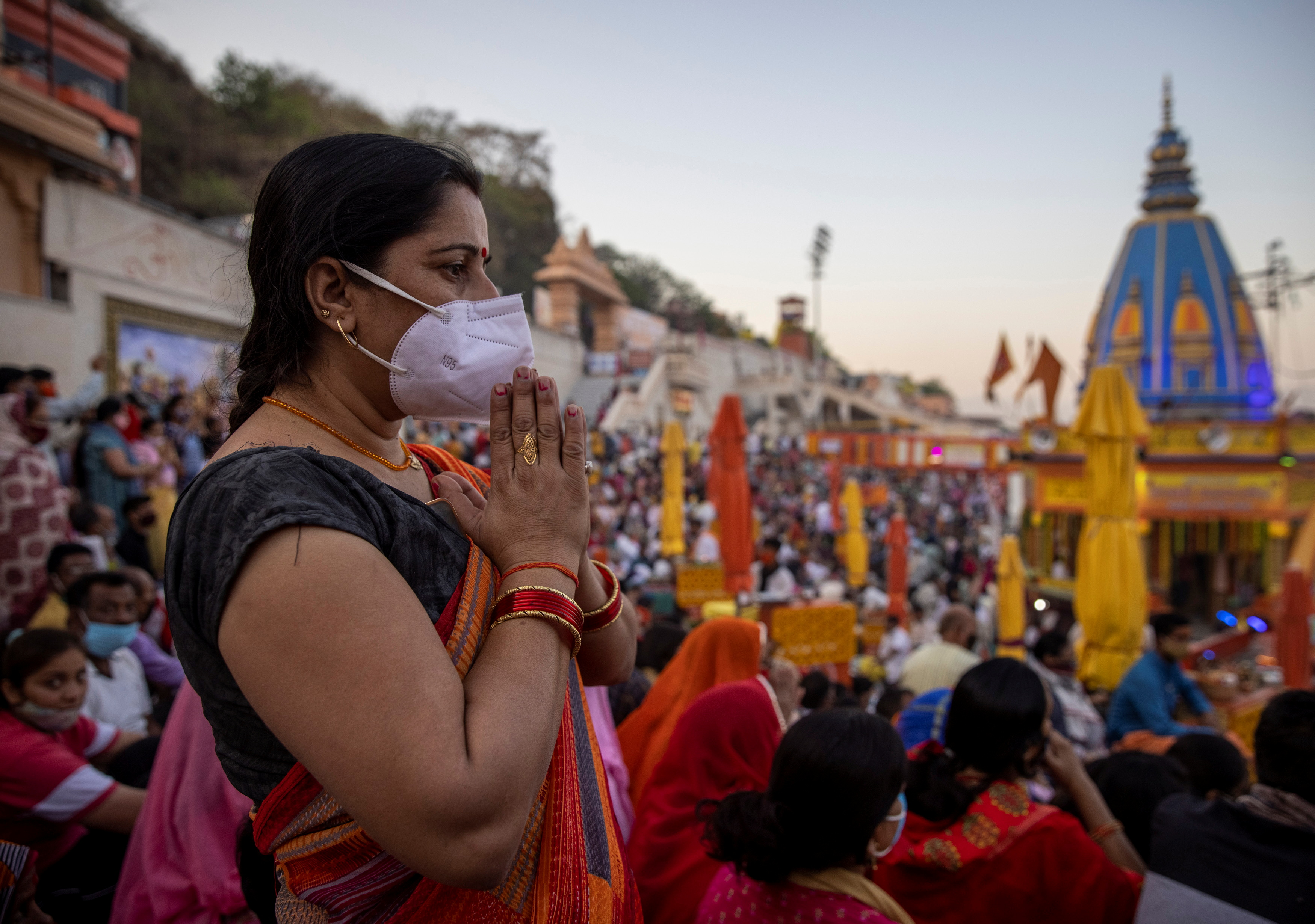 A devotee attends an evening prayer on the banks of Ganges river during Kumbh Mela, or the Pitcher Festival, amidst the spread of the coronavirus disease (COVID-19), in Haridwar, India, April 10, 2021. REUTERS/Danish Siddiqui