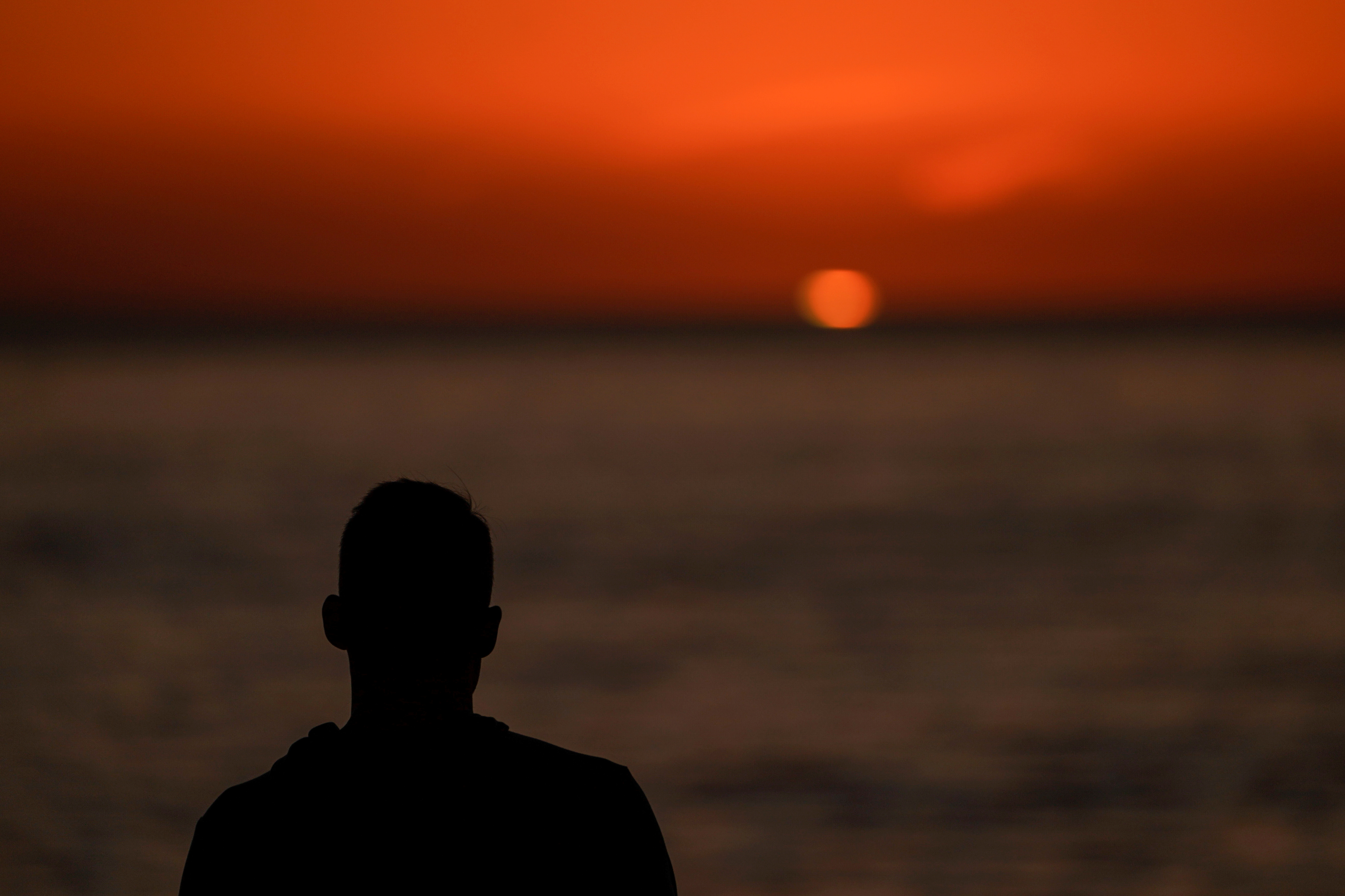 A man watches the sun set over the Pacific Ocean in Encinitas, California, U.S. October 7, 2019.   REUTERS/Mike Blake/File Photo