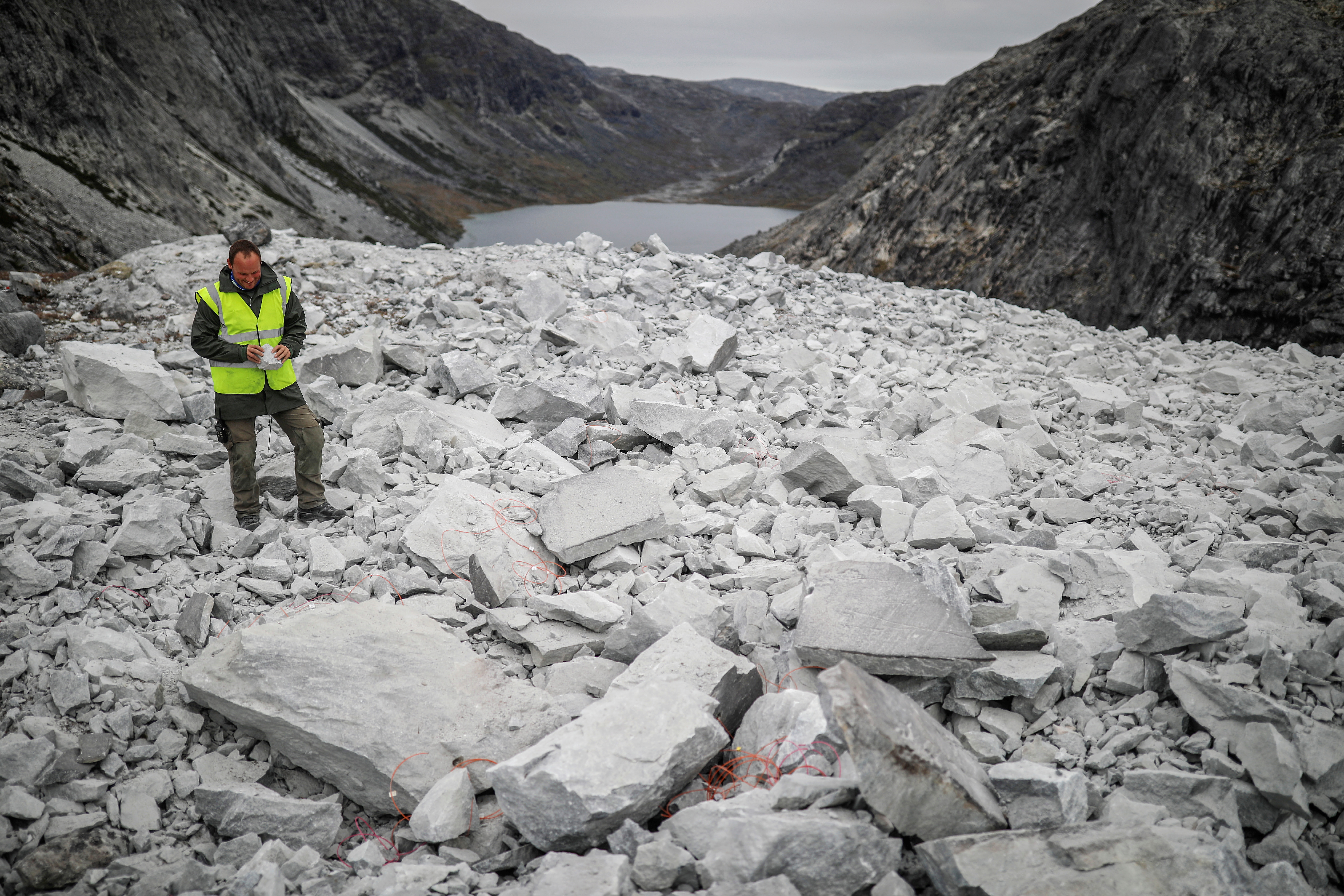 A worker of the company Greenland Anorthosite Mining checks stones after an explosion at an exploration site of an anorthosite deposit close to the Qeqertarsuatsiaat fjord, Greenland, September 11, 2021. REUTERS/Hannibal Hanschke