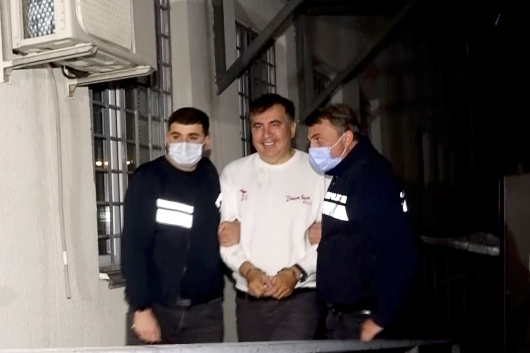Georgia's former President Mikheil Saakashvili, who was detained after returning to the country, is escorted by police officers as he arrives at a prison in Rustavi, Georgia October 1, 2021, in this still image taken from video. Georgian Interior Ministry/Handout via REUTERS