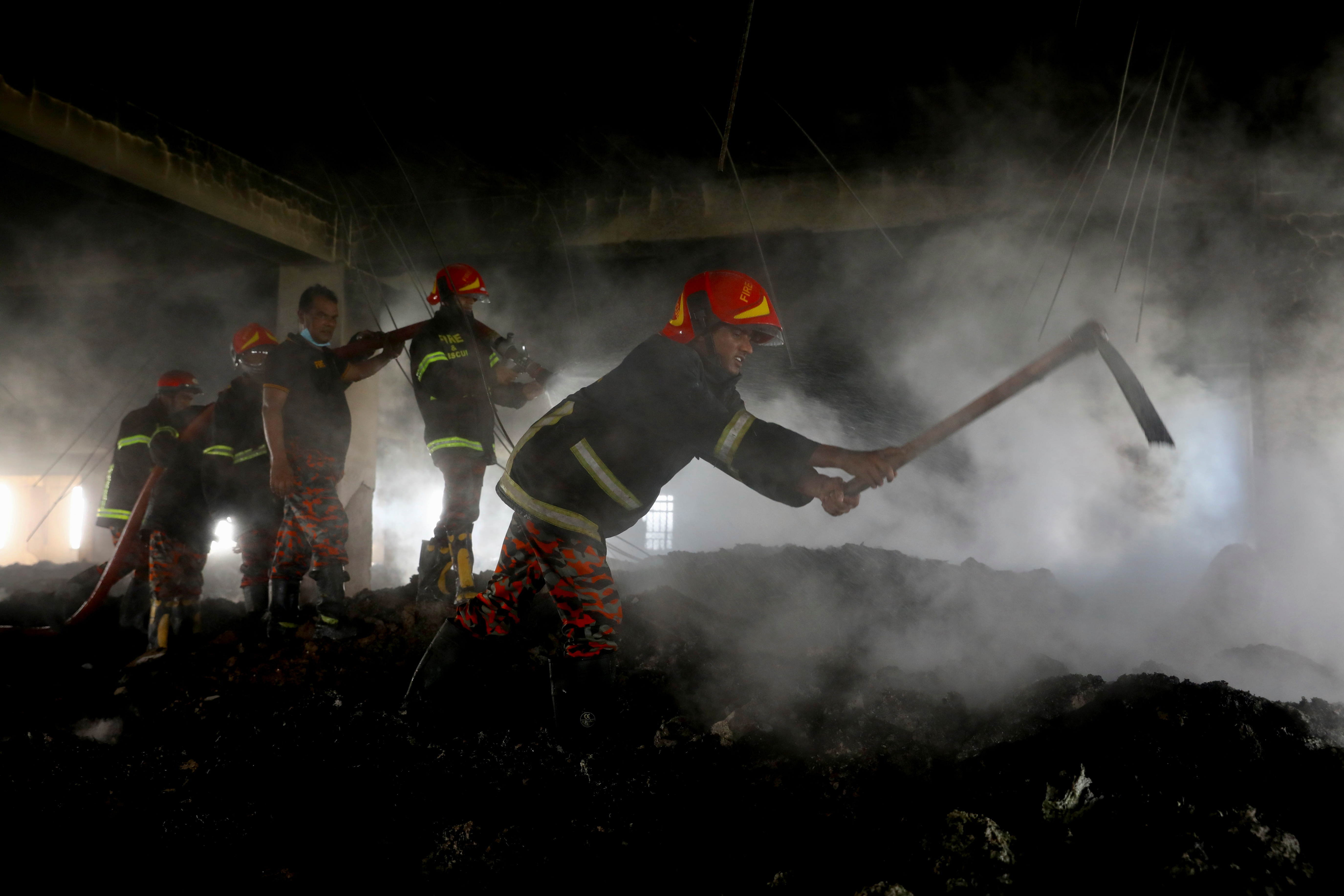 Firefighters work at the site of a fire that broke out on Thursday at Hashem Foods Ltd factory in Rupganj, Narayanganj district, on the outskirts of Dhaka, Bangladesh, July 10, 2021. REUTERS/Mohammad Ponir Hossain