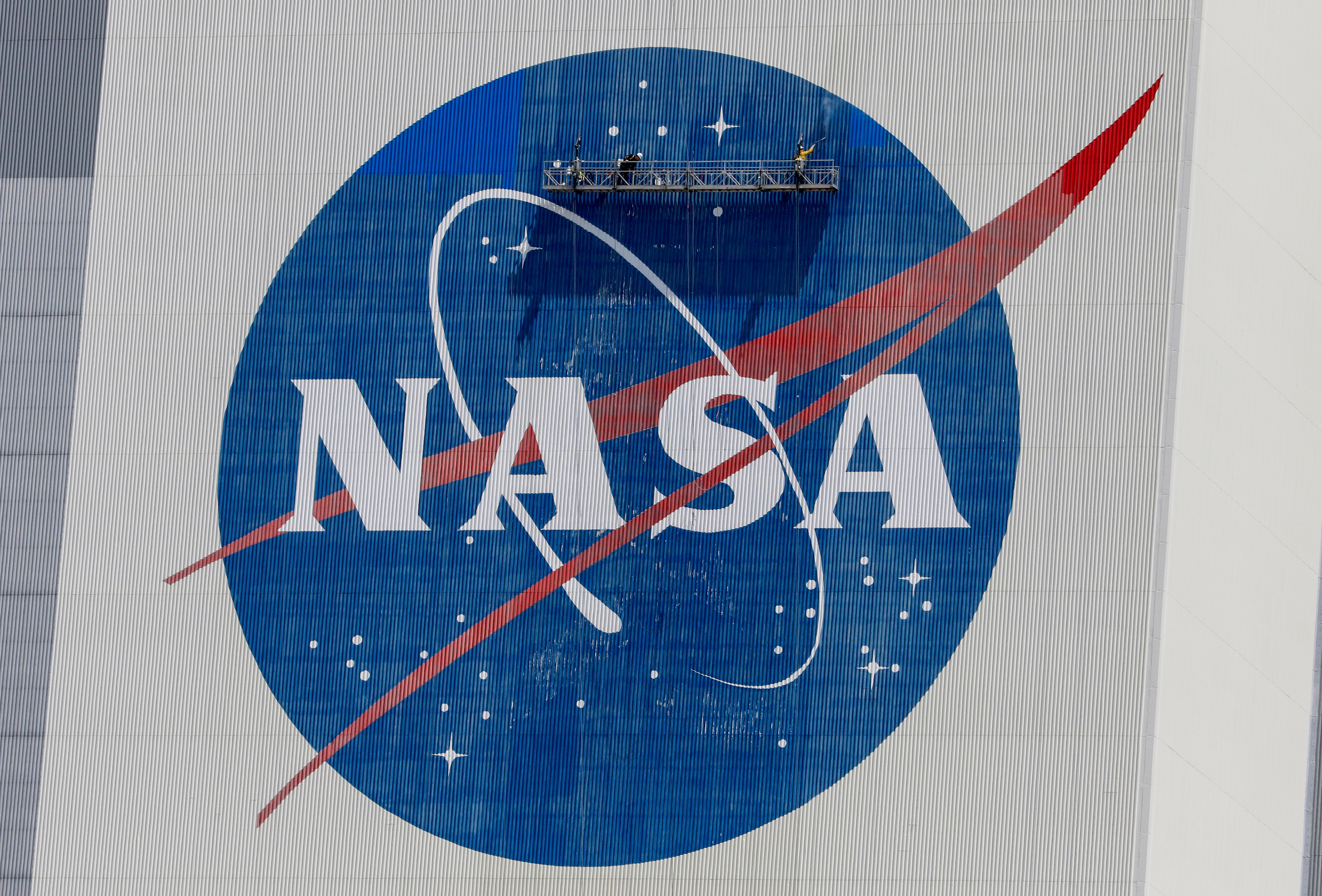 Workers pressure wash the logo of NASA on the Vehicle Assembly Building before SpaceX will send two NASA astronauts to the International Space Station aboard its Falcon 9 rocket, at the Kennedy Space Center in Cape Canaveral, Florida, U.S., May 19, 2020. REUTERS/Joe Skipper/File Photo