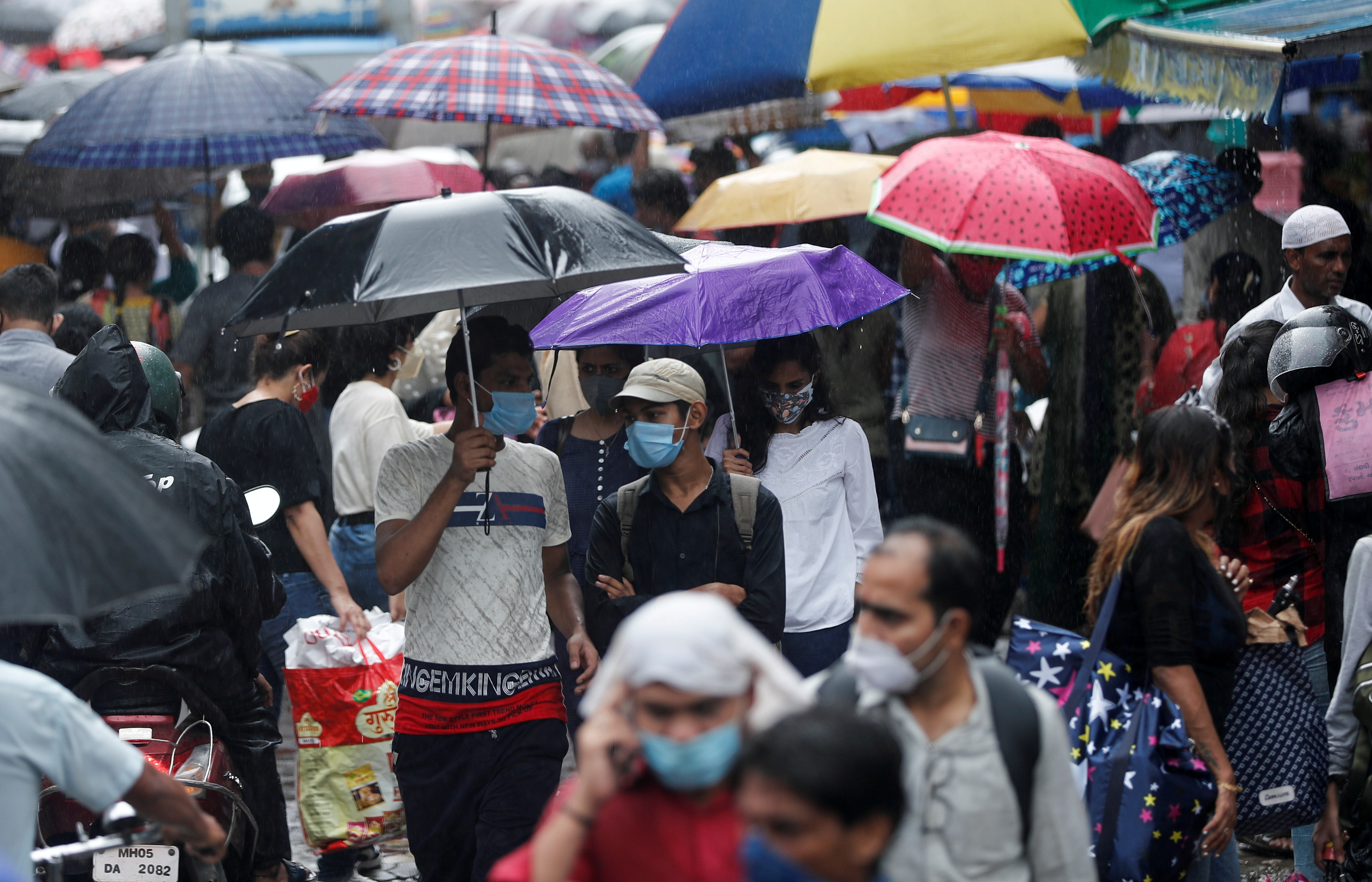 People walk through a crowded market on a rainy day amidst the spread of the coronavirus disease (COVID-19) in Mumbai, India, July 14, 2021. REUTERS/Francis Mascarenhas/File Photo