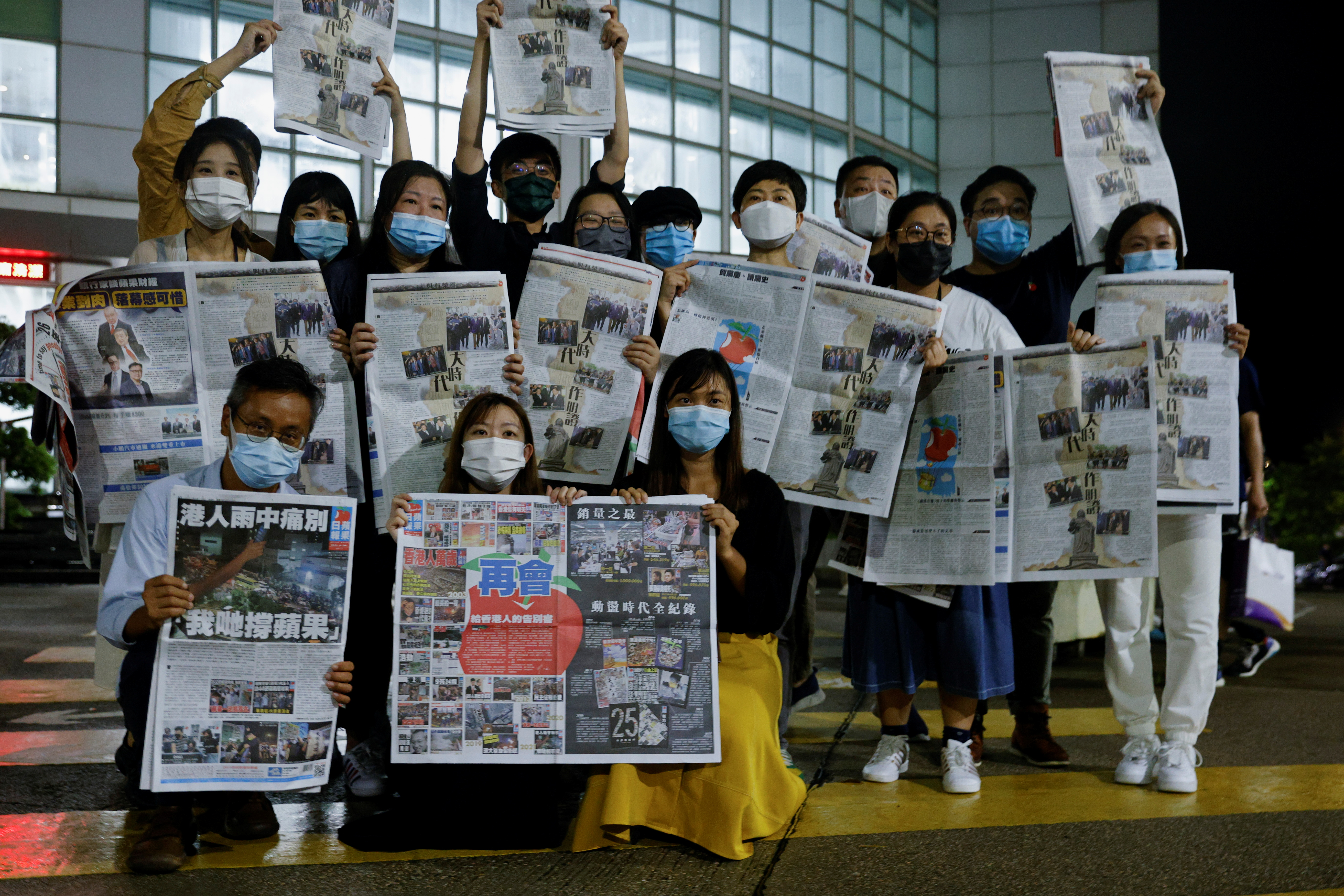 Staff members of Apple Daily and its publisher Next Digital pose with the final edition of Apple Daily at its headquarters in Hong Kong, China June 24, 2021. REUTERS/Tyrone Siu