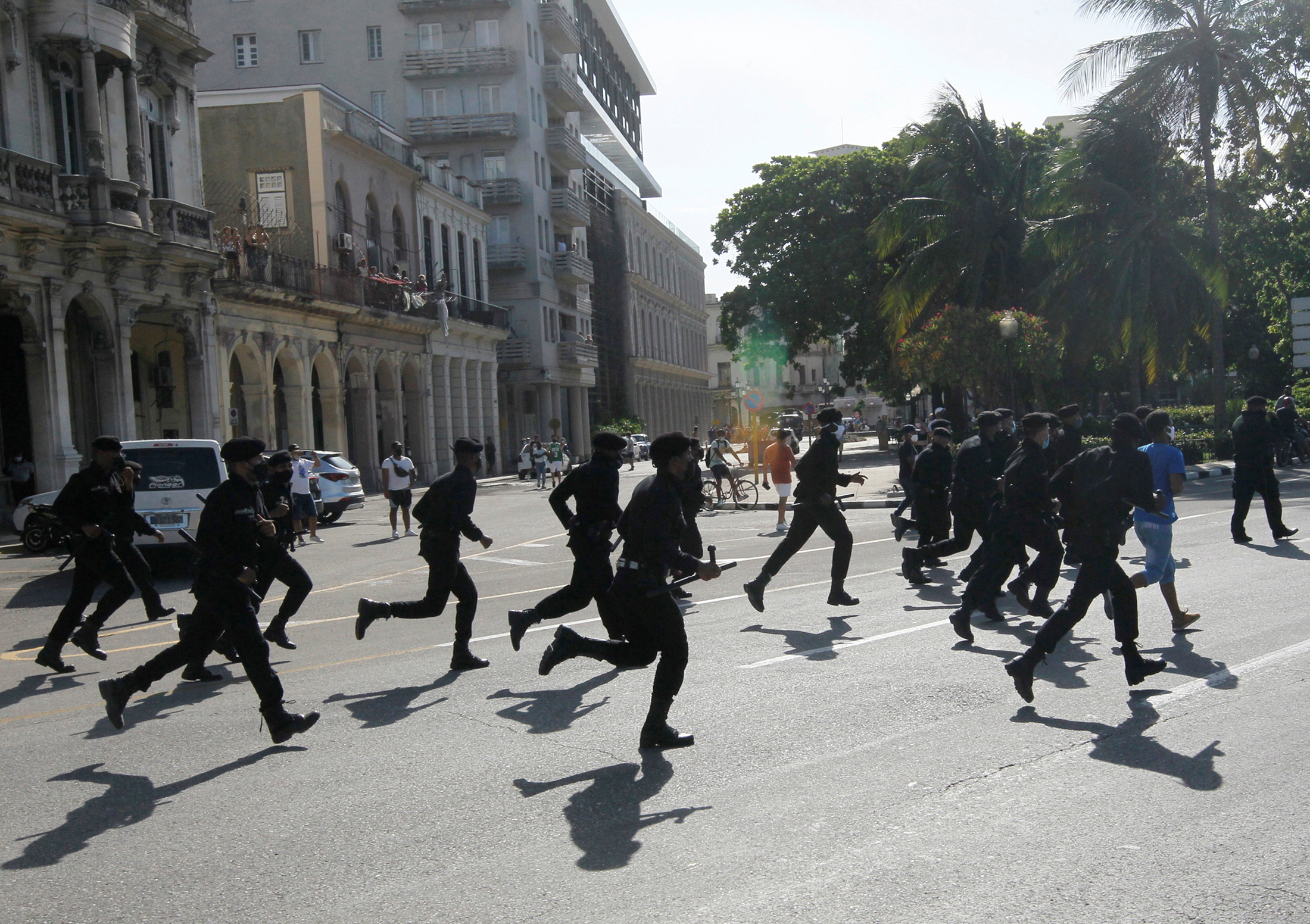 Police run during protests against and in support of the government, amidst the coronavirus disease (COVID-19) outbreak, in Havana, Cuba July 11, 2021.  REUTERS/Stringer