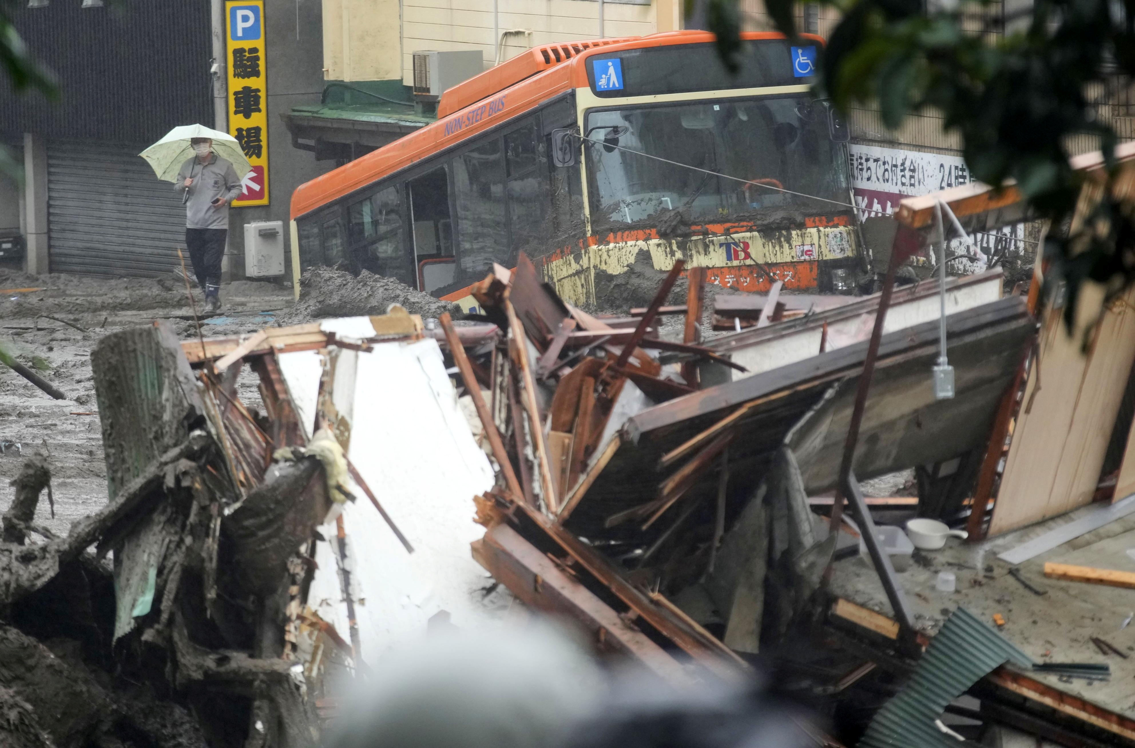 A damaged bus and debris of the houses are seen at a mudslide site following heavy rain at Izusan district in Atami, Japan July 3, 2021. Kyodo/via REUTERS