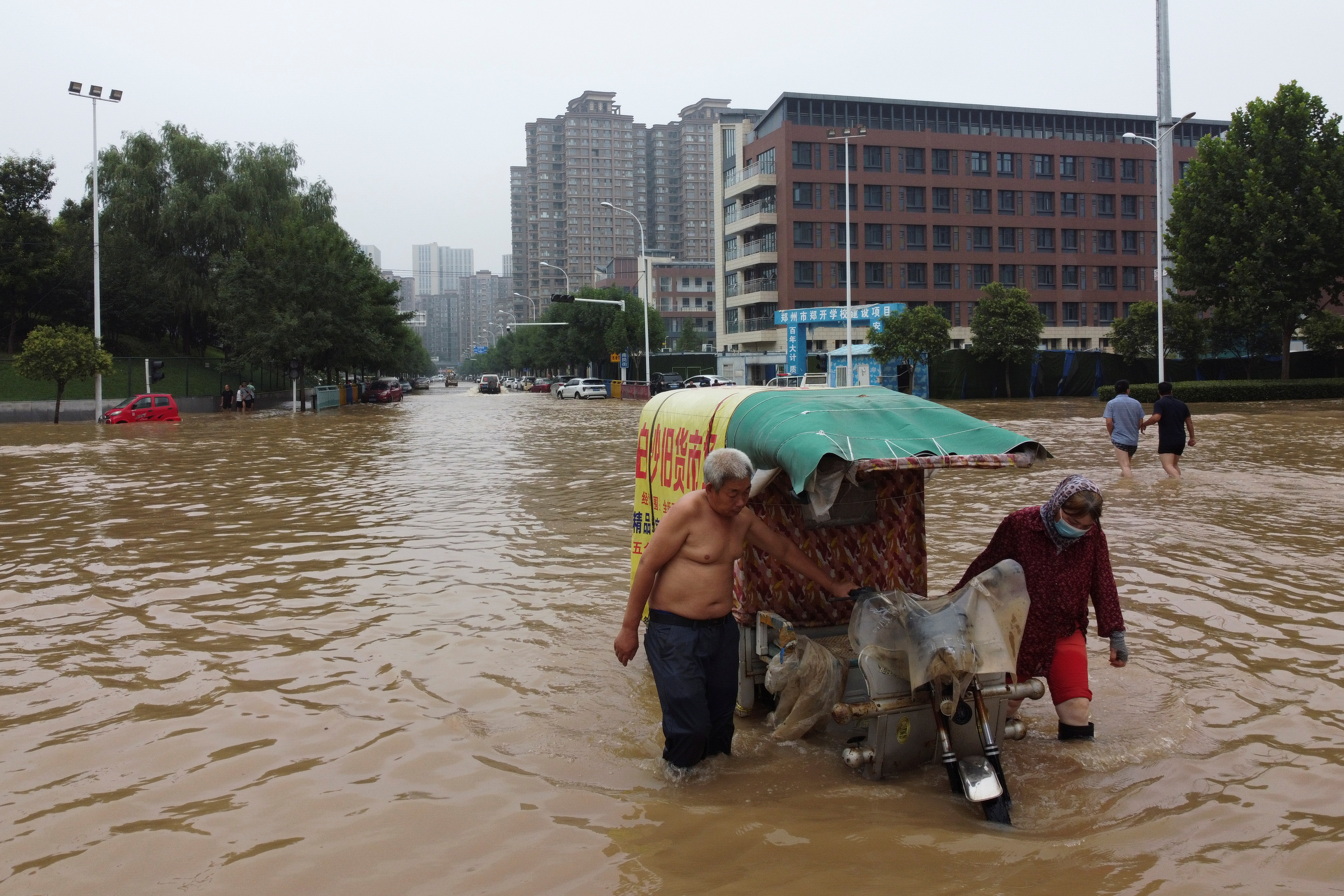 People push a vehicle through floodwaters following heavy rainfall in Zhengzhou, Henan province, China July 23, 2021. Picture taken with a drone. REUTERS/Aly Song