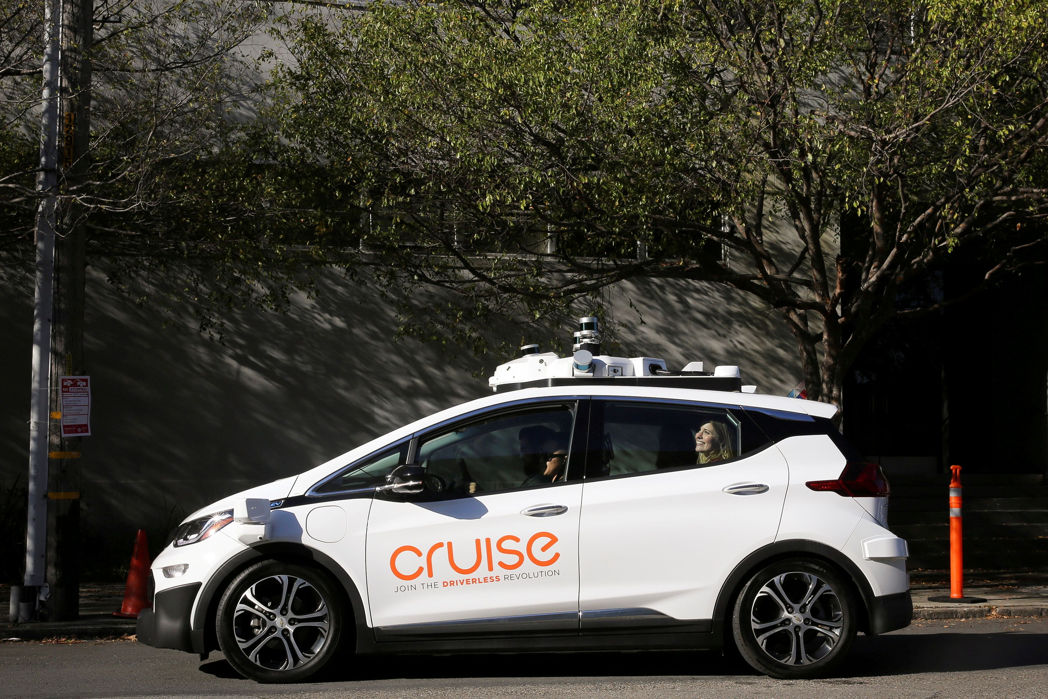 A woman smiles in the back seat of a self-driving Chevy Bolt EV car during a media event by Cruise, GM's autonomous car unit, in San Francisco, California, U.S., Nov. 28, 2017. REUTERS/Elijah Nouvelage/File Photo