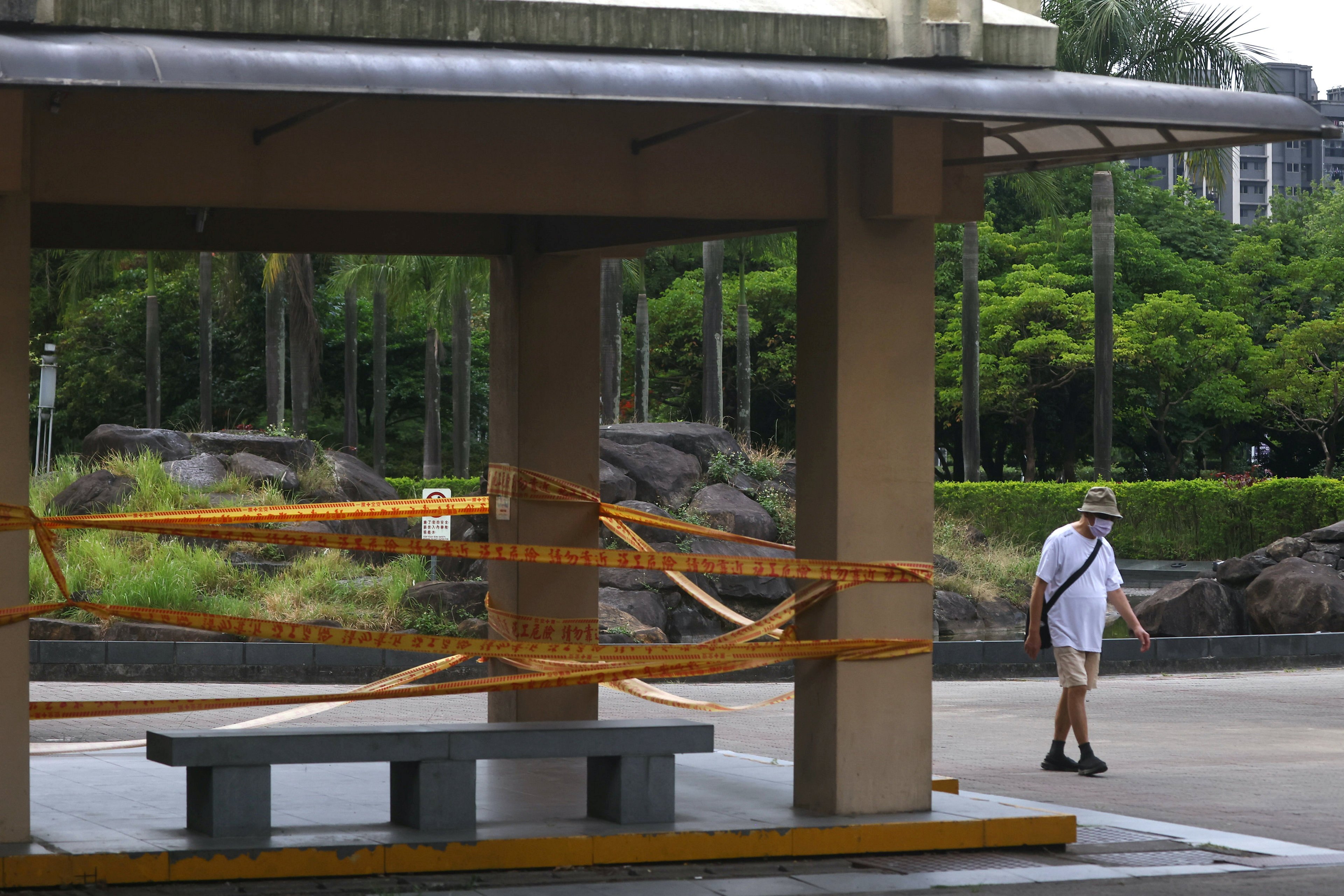 A man wearing a protective mask walks past a closed park following the recent rise in coronavirus disease (COVID-19) infections in Taipei, Taiwan May 21, 2021. REUTERS/Ann Wang