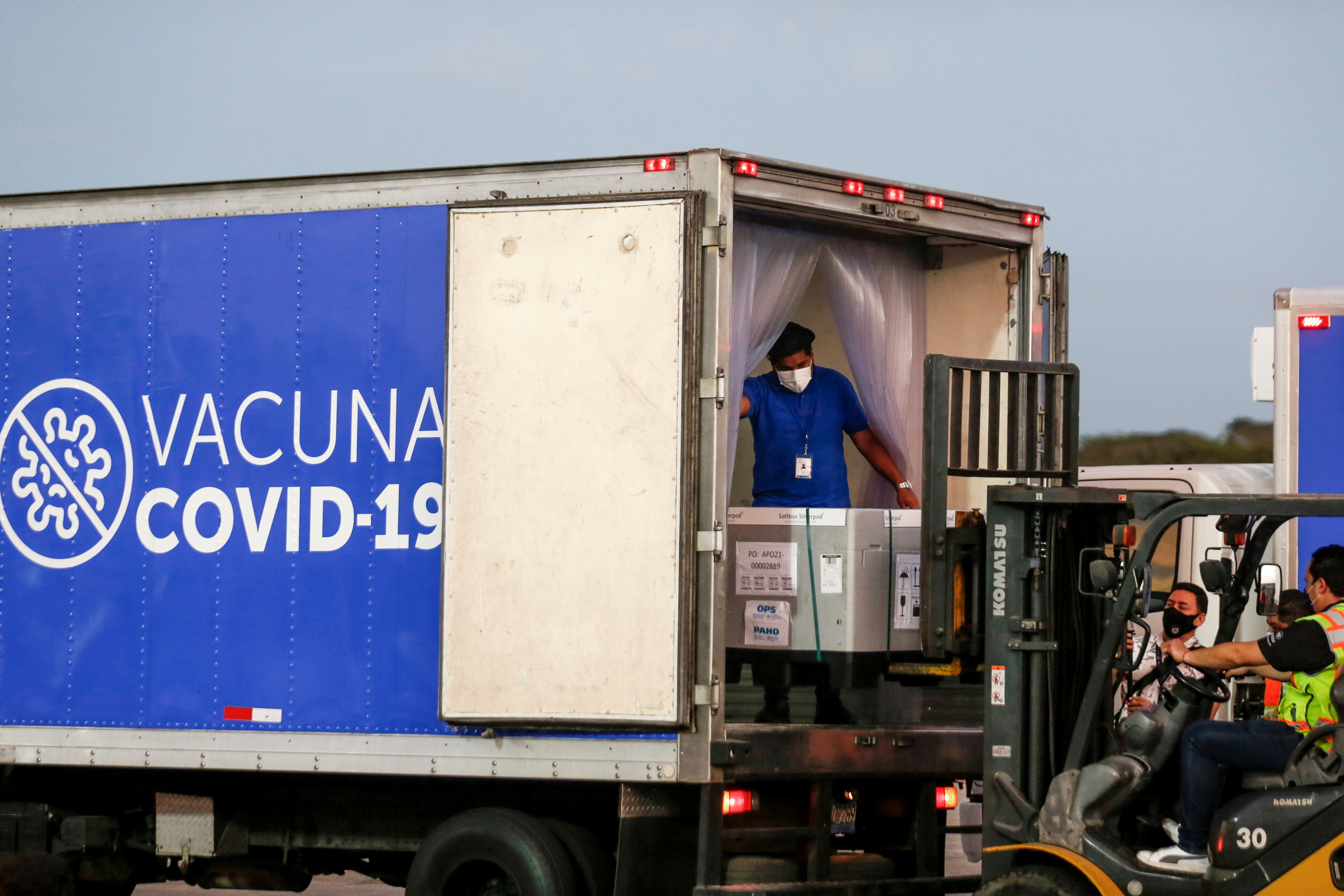 Containers of AstraZeneca (SKBio Corea) vaccines under the COVAX scheme against the coronavirus disease (COVID-19) are loaded onto a truck after arriving at the Mons. Oscar Arnulfo Romero International Airport, in San Luis Talpa, El Salvador March 11, 2021. REUTERS/Jose Cabezas