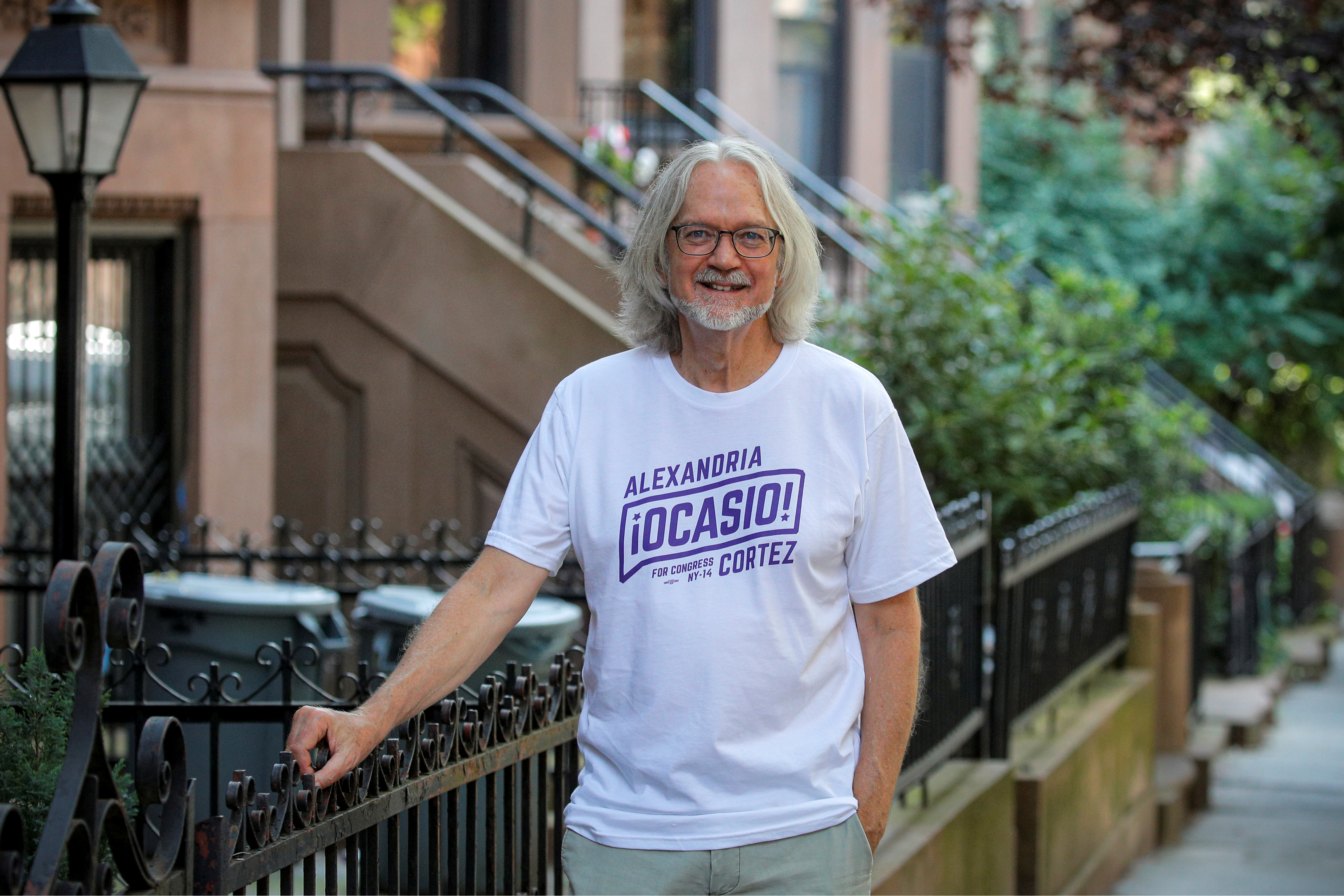 Peter Hogness poses wearing his Alexandria Ocasio-Cortez branded T-shirt in the Park Slope area of Brooklyn in New York City, U.S., July 16, 2021. Picture taken July 16, 2021.  REUTERS/Brendan McDermid