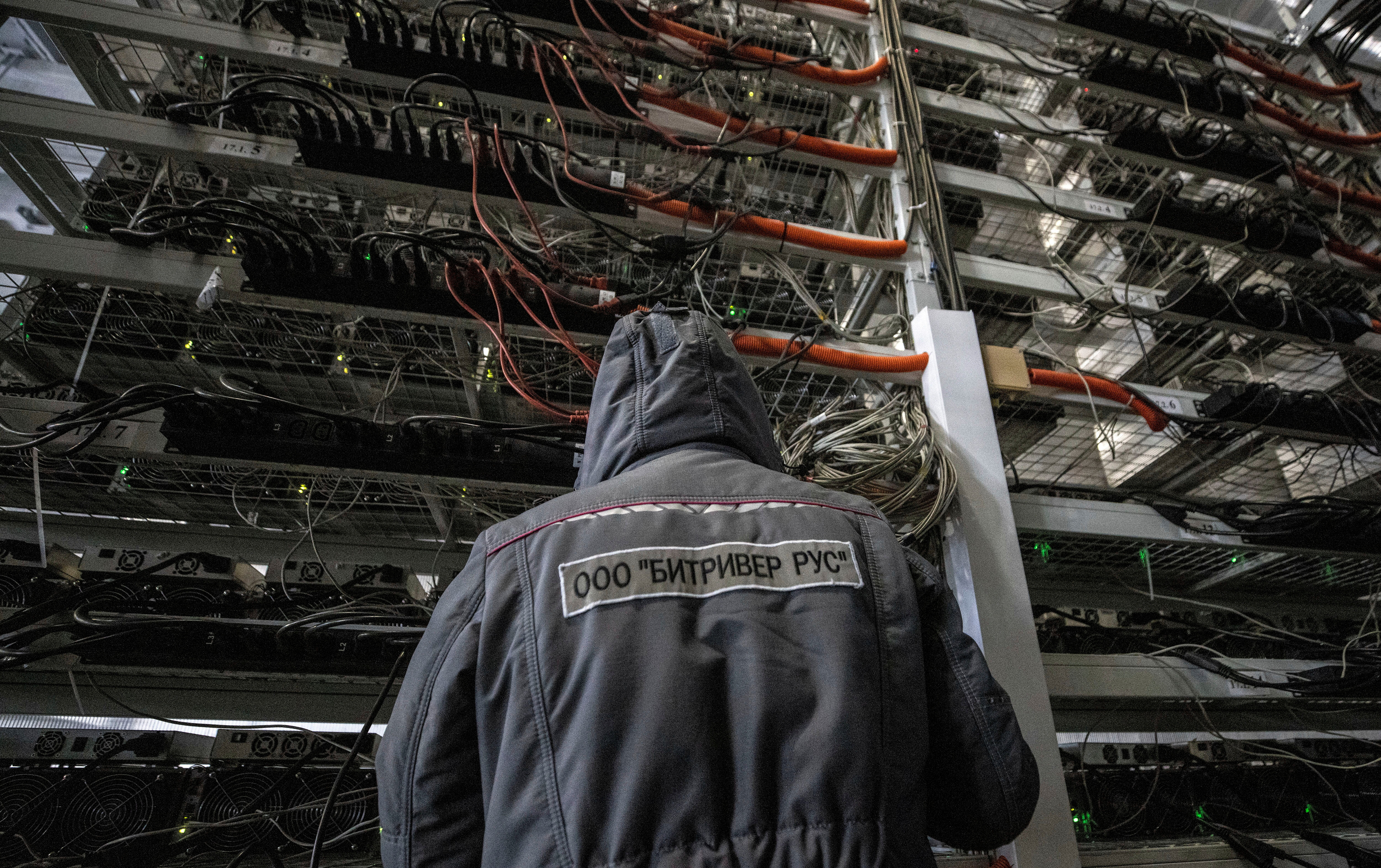 An employee works at the data centre of BitRiver company providing services for cryptocurrency mining in the city of Bratsk in Irkutsk Region, Russia March 2, 2021. BitRiver offers hosting services and turnkey solutions for cryptocurrency mining operations to institutional investors including bitcoin mining firms. Picture taken March 2, 2021. REUTERS/Maxim Shemetov/File Photo