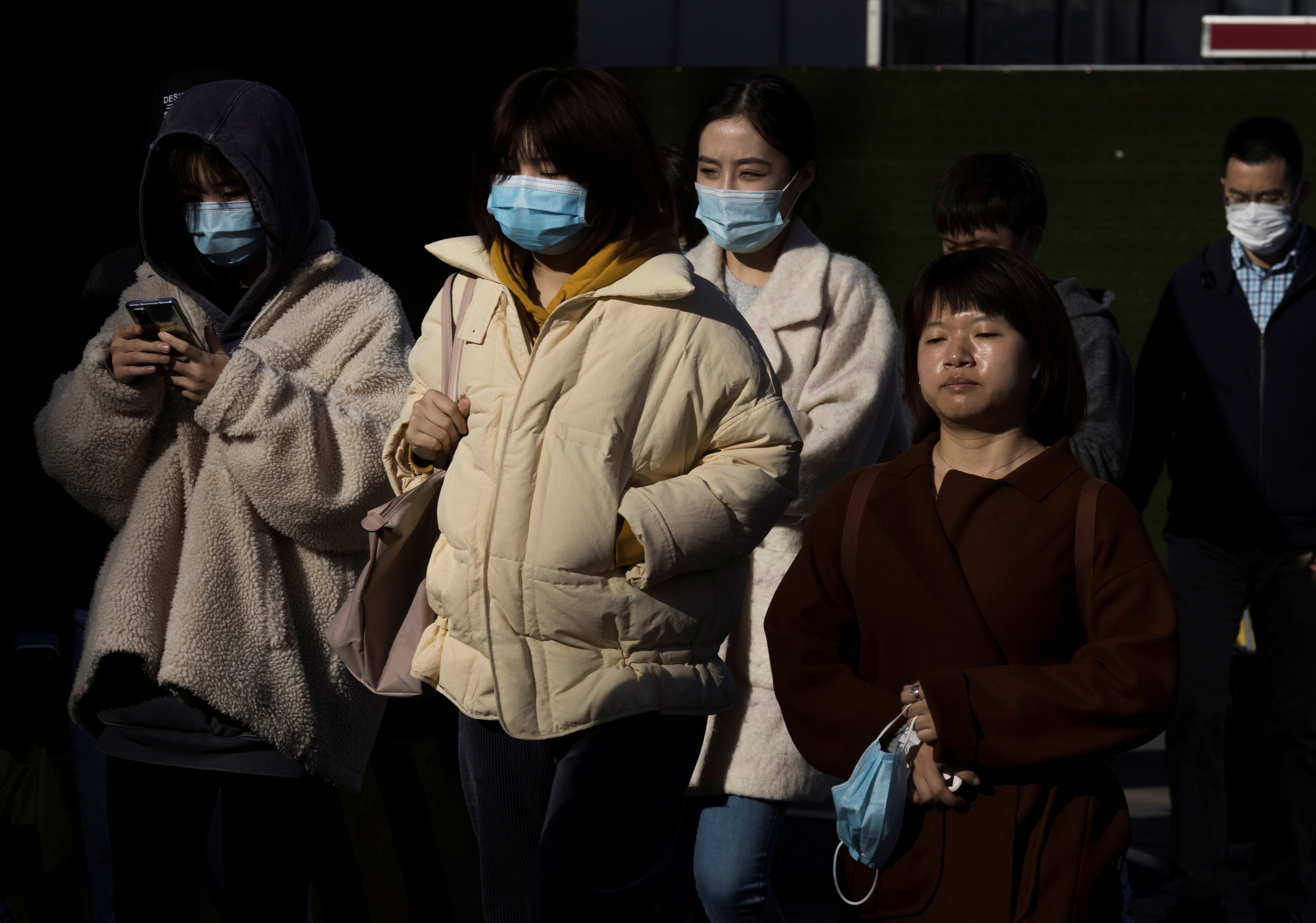 People walk in a street during morning rush hour following an outbreak of the coronavirus disease (COVID-19) in Beijing, China, November 3, 2020.   REUTERS/Thomas Peter