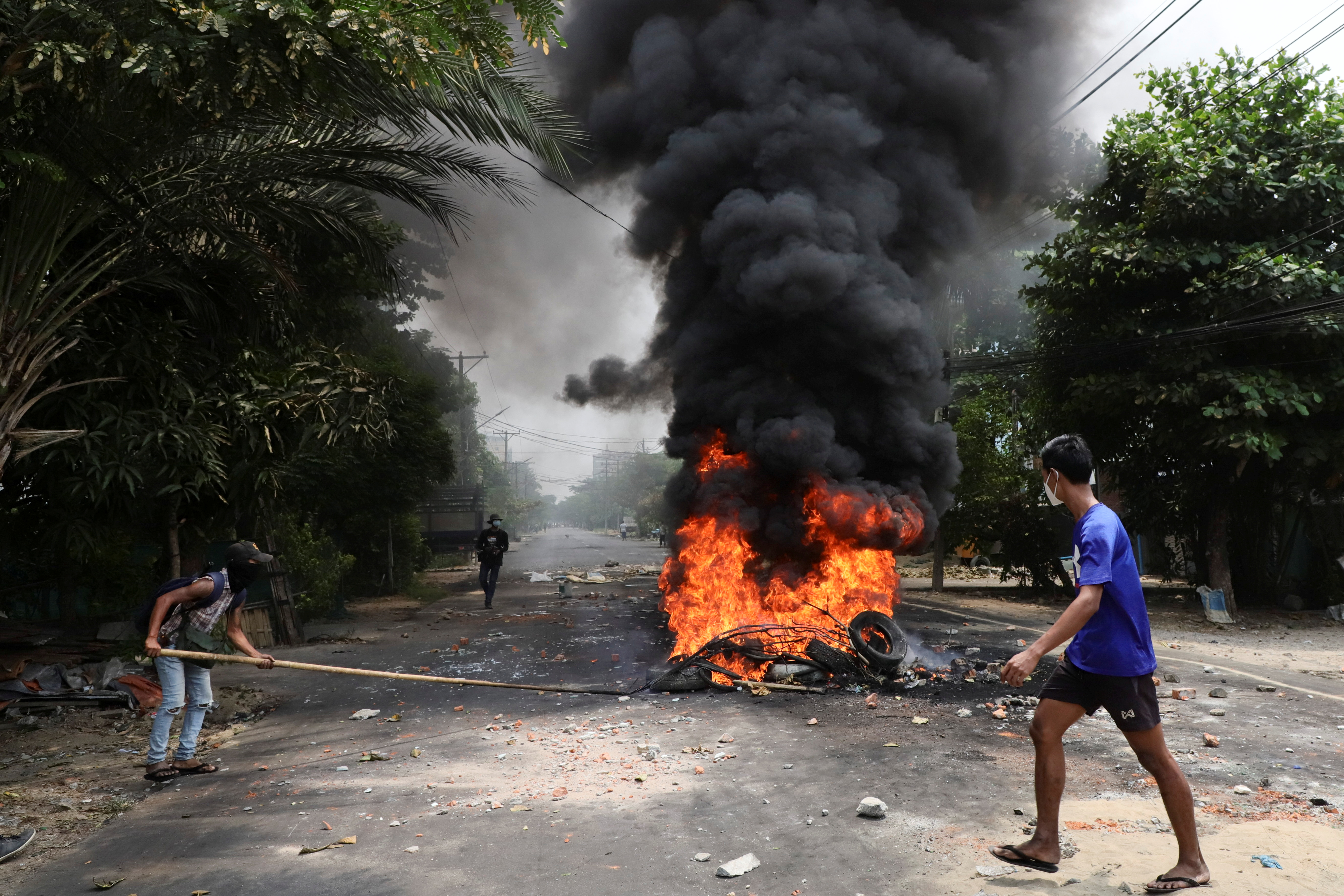 An anti-coup protester walks past burning tires after activists launched a