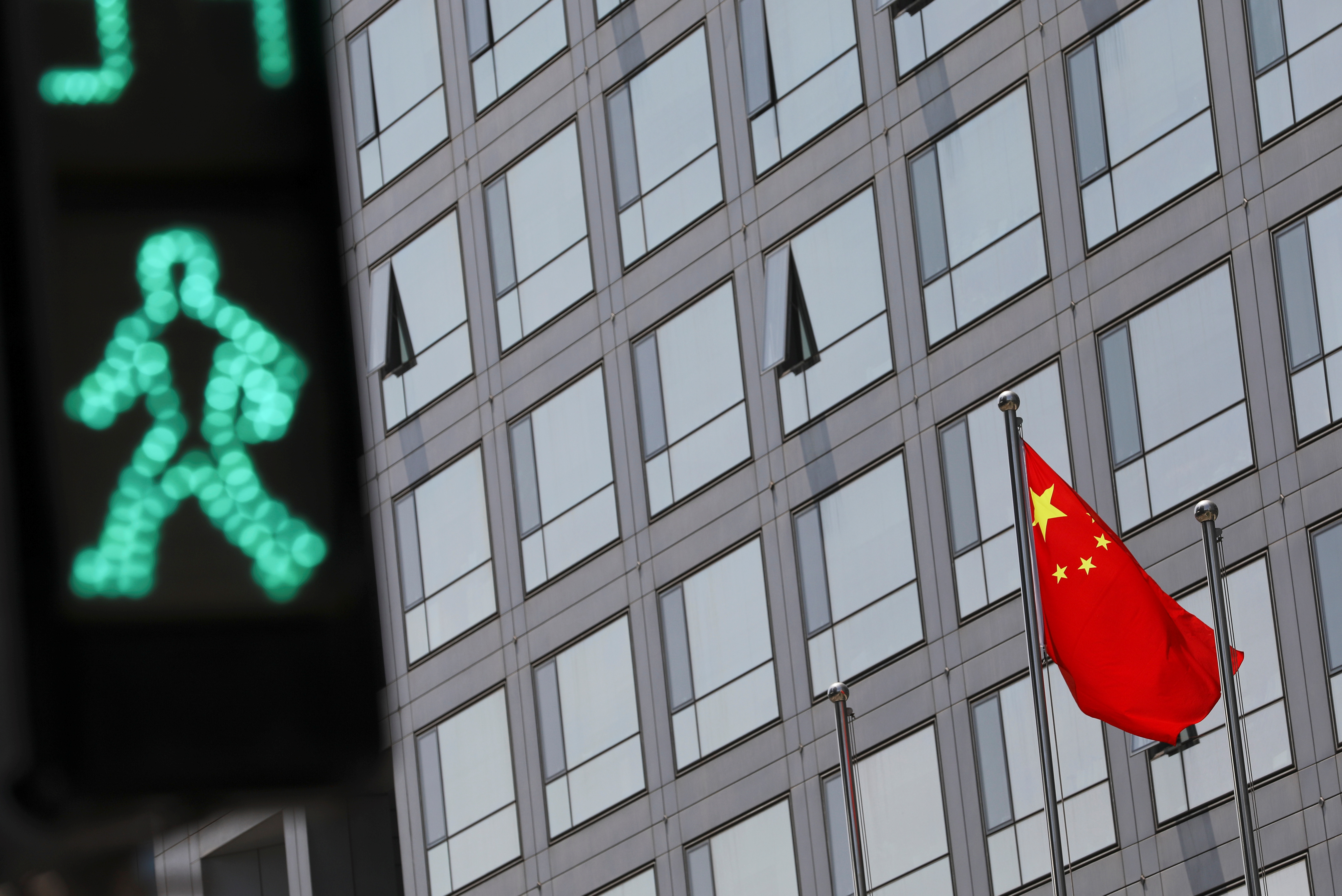 A Chinese national flag flutters outside the China Securities Regulatory Commission (CSRC) building on the Financial Street in Beijing, China July 9, 2021. REUTERS/Tingshu Wang