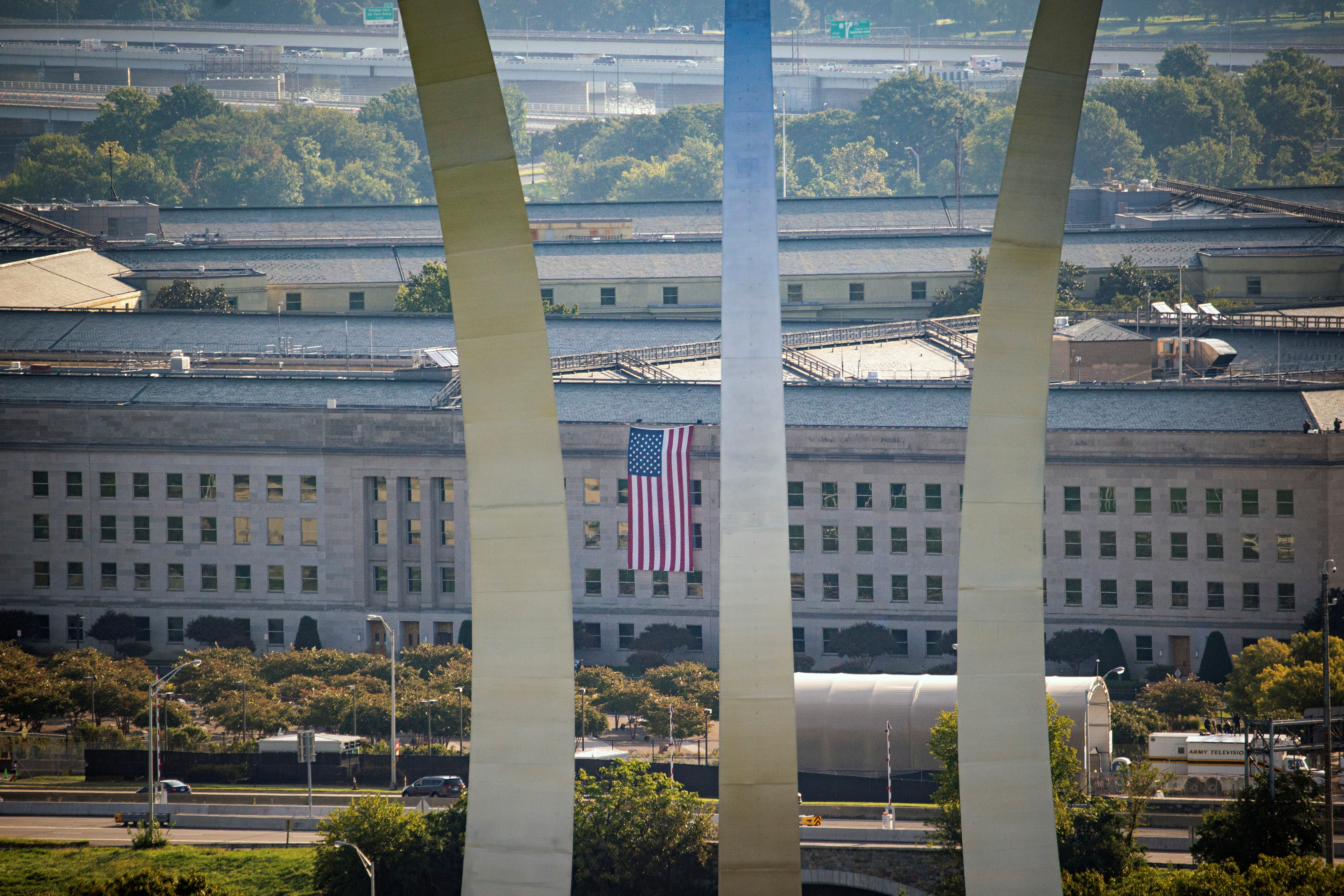 The U.S. Air Force Memorial is seen in the foreground as an American flag is unfurled from the roof of the Pentagon at the site where a jetliner hit the building, during ceremonies commemorating the 20th anniversary of the September 11, 2001 attacks in Arlington, Virginia, U.S., September 11, 2021. This photo was taken at 8.46am EDT on September 11, 2021, exactly 20 years after the first plane struck the North Tower of the World Trade Center in New York. REUTERS/Al Drago