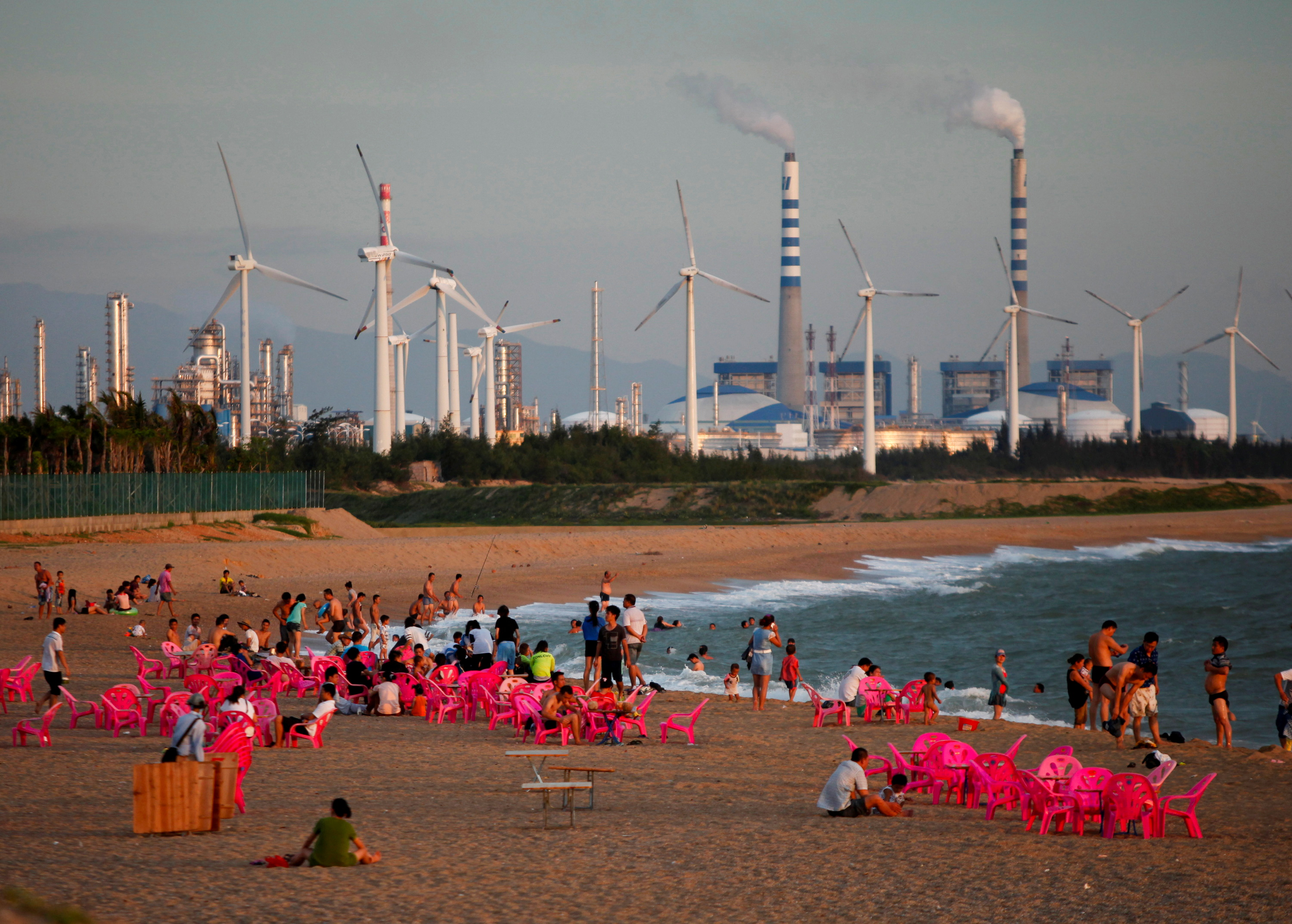 Windmills and a power plant can be seen in the distance as beachgoers watch sunset in the city of Dongfang on the western side of China's island province of Hainan, June 18, 2014. REUTERS/John Ruwitch/File Photo
