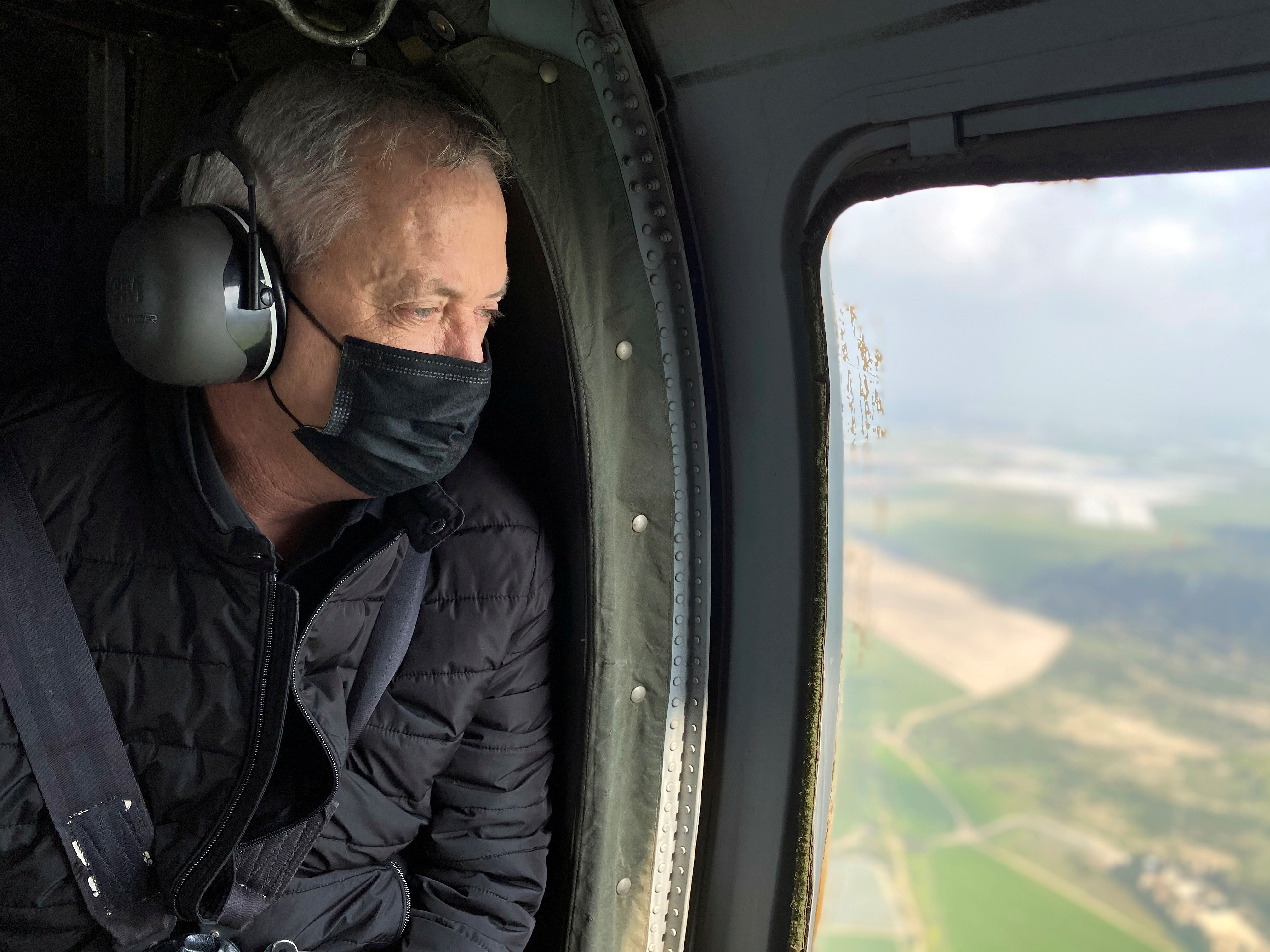 Israeli Defence Minister Benny Gantz wears a face mask as he looks out from the window of a helicopter during a tour of the Gaza border area, southern Israel, March 2, 2021. REUTERS/Dan Williams/File Photo