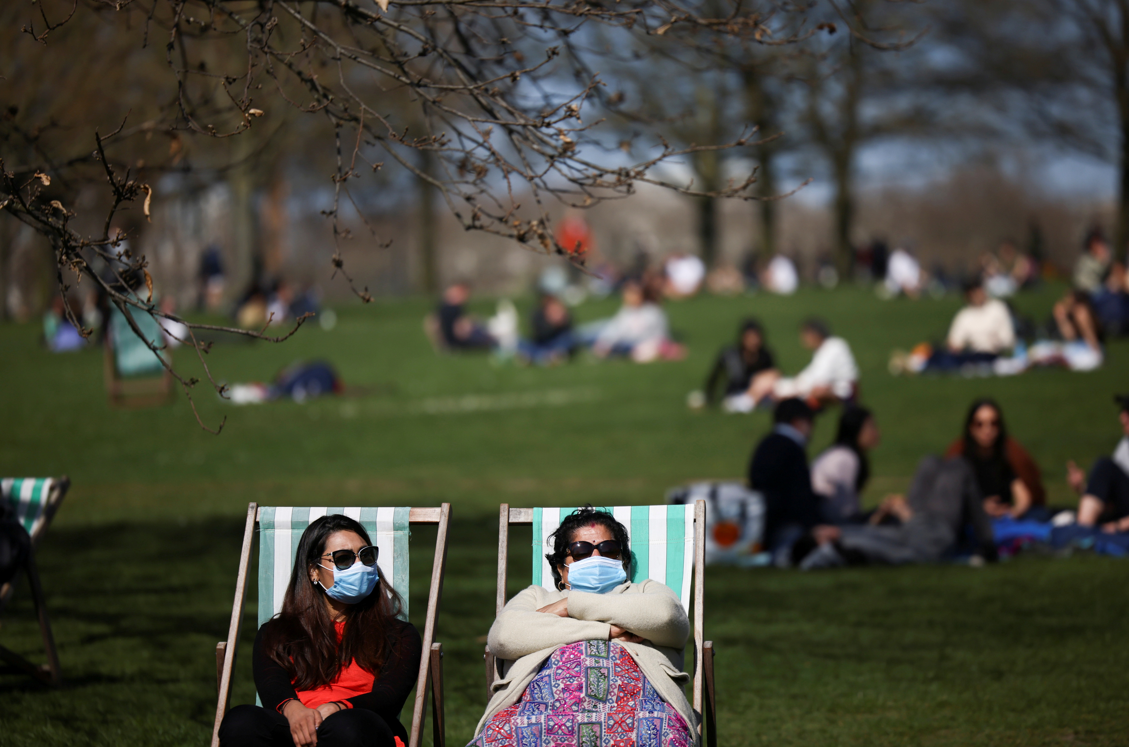 People relax during sunny weather in Hyde Park, amid the coronavirus disease (COVID-19) outbreak, in London, Britain, April 4, 2021. REUTERS/Henry Nicholls/File Photo