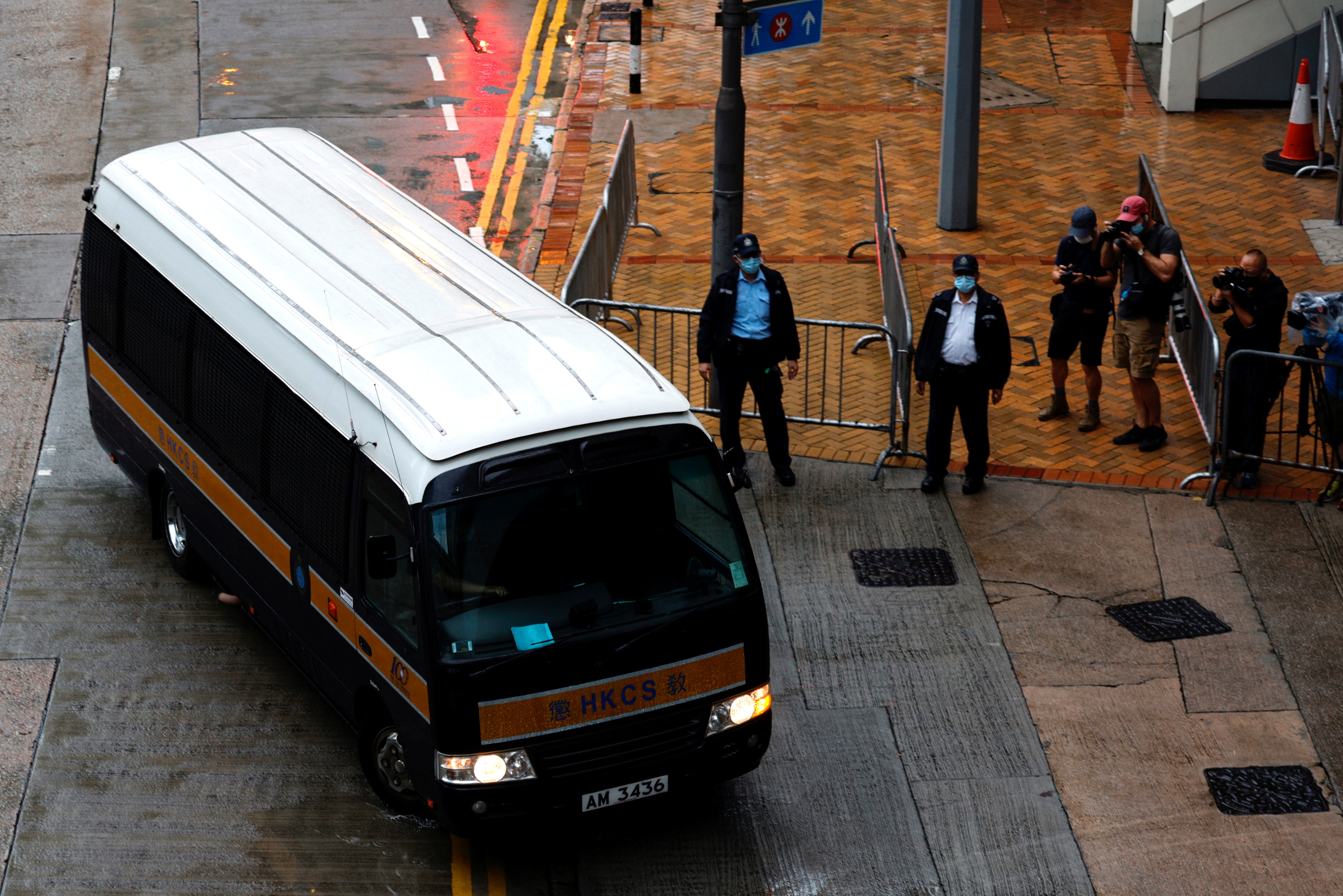 A prison van arrives as police stand guard for Tong Ying-kit's arrival, the first person charged under a new national security law, in Hong Kong, China, July 30, 2021. REUTERS/Tyrone Siu