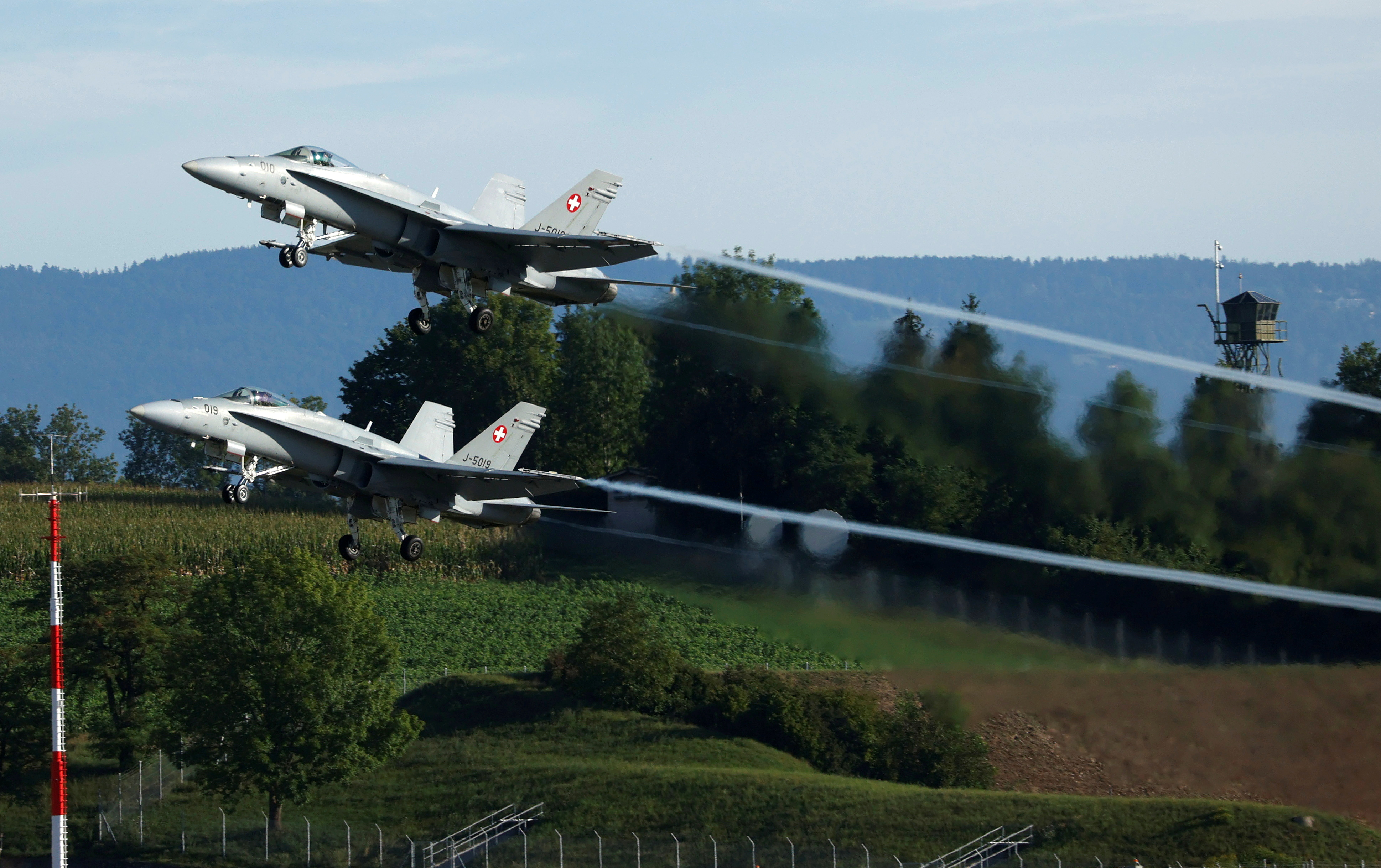 Two F/A-18 Hornet fighter jets of the Swiss Air Force take off at the Swiss Army base in Payerne, Switzerland, August 25, 2020. REUTERS/Denis Balibouse/File Photo