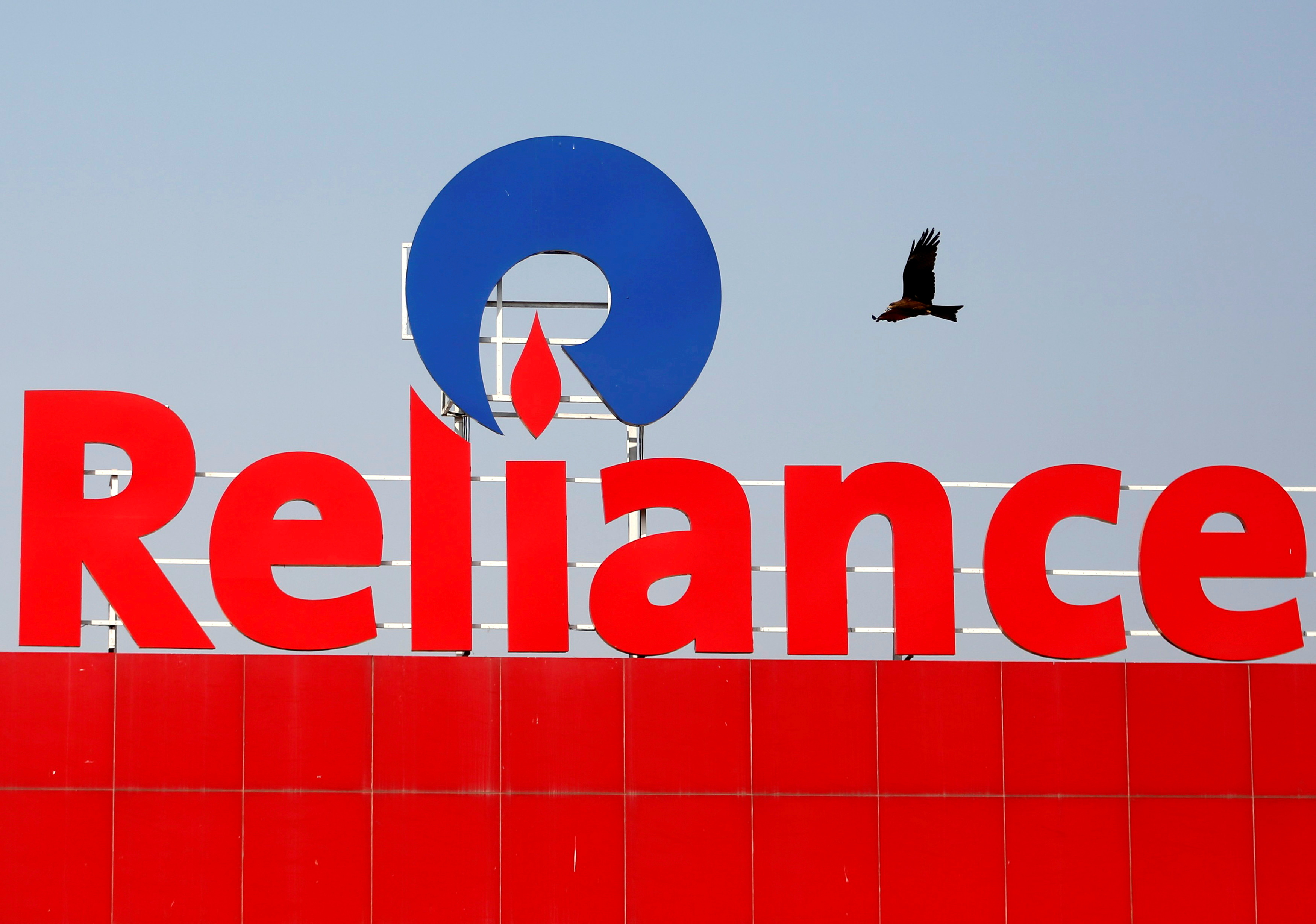 A bird flies past a Reliance Industries logo installed on its mart in Ahmedabad, India January 16, 2017. REUTERS/Amit Dave//File Photo