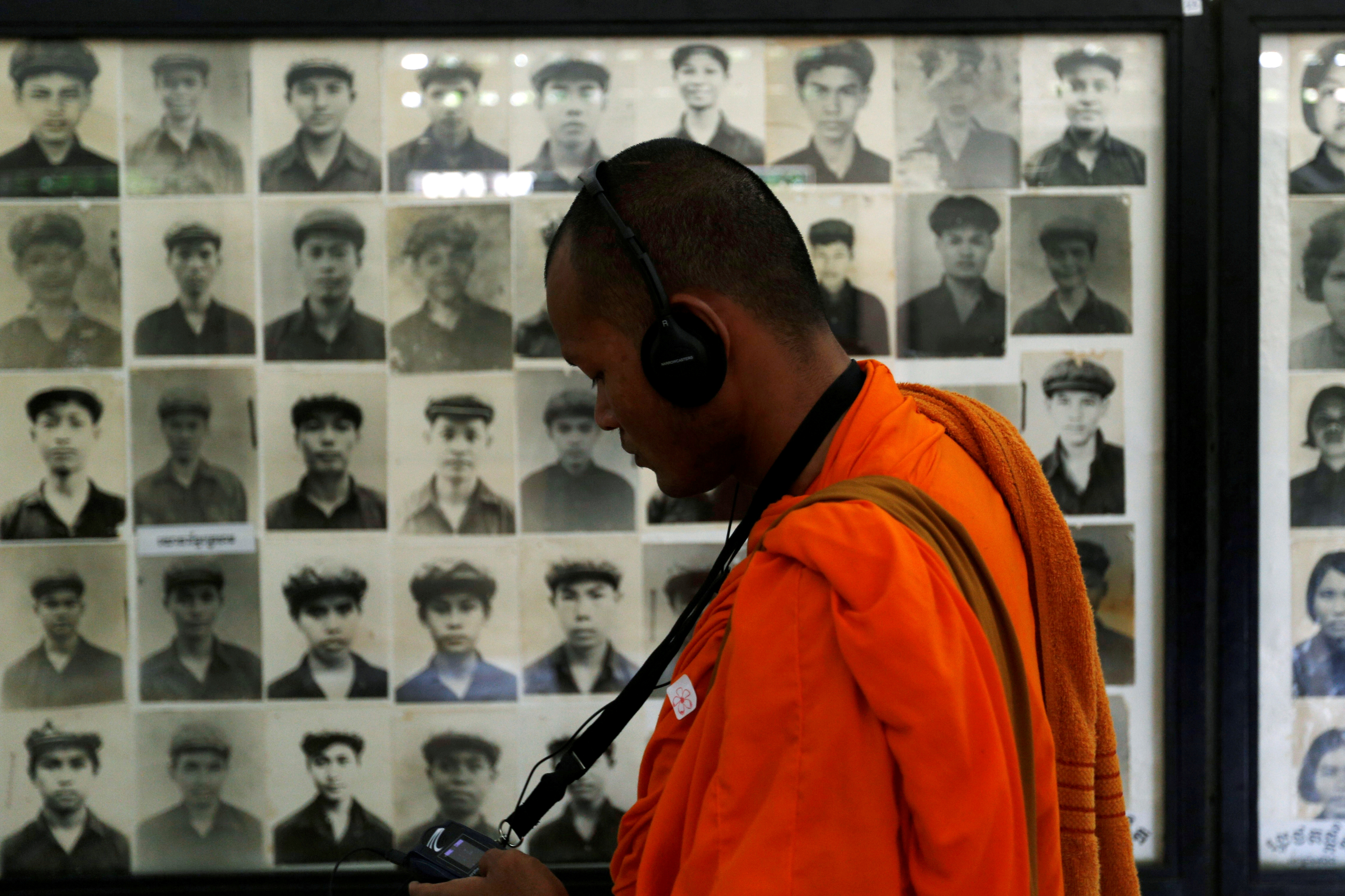 A Buddhist monk looks at pictures of victims of the Khmer Rouge regime at Tuol Sleng Genocide Museum in Phnom Penh, Cambodia June 1, 2016. REUTERS/Samrang Pring