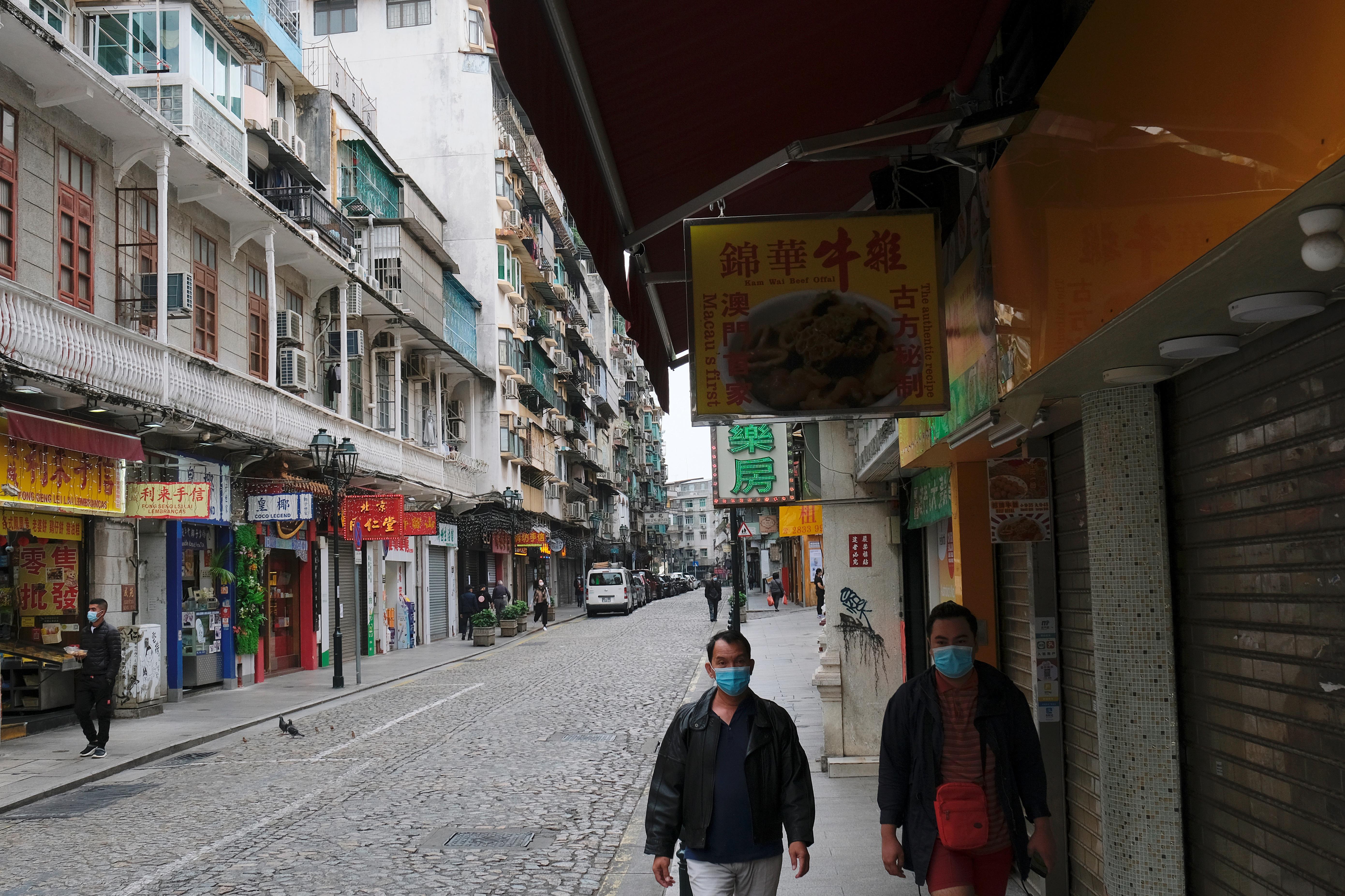 People wear masks as they walk near Ruins of St. Paul's, following the coronavirus outbreak in Macau, China February 5, 2020. REUTERS/Tyrone Siu