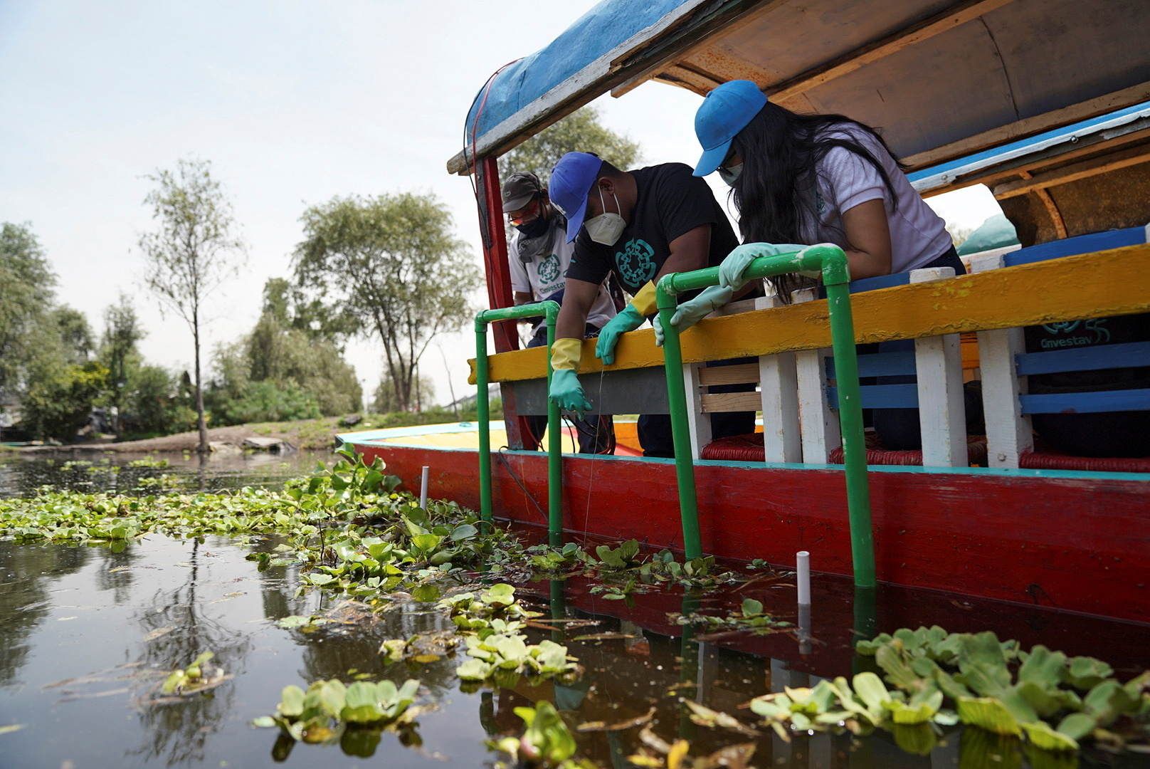 """Members of a team of researchers from the Center for Research and Advanced Studies (Cinvestav), who developed a method that converts solar energy into photovoltaic energy that activates a pump that sends """"nanobubbles"""" into the water, install a water system at a trajinera boat as part of a project to clean the polluted waters at the canals of Xochimilco, in Mexico City, Mexico August 20, 2021. REUTERS/Toya Sarno Jordan"""