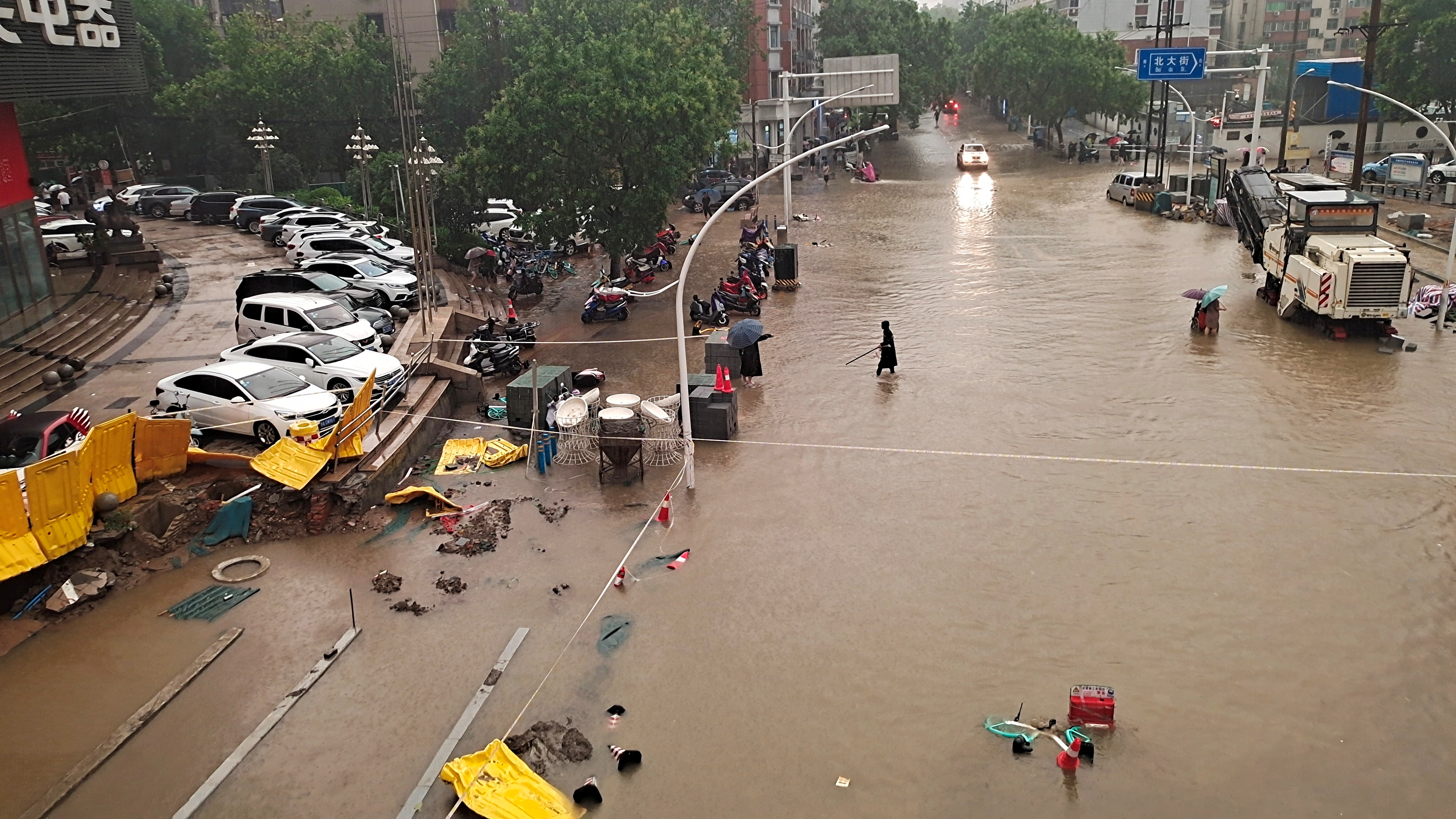 People wade through floodwaters on a road amid heavy rainfall in Zhengzhou, Henan province, China July 20, 2021. Picture taken July 20, 2021. China Daily via REUTERS  ATTENTION EDITORS - THIS IMAGE WAS PROVIDED BY A THIRD PARTY. CHINA OUT.