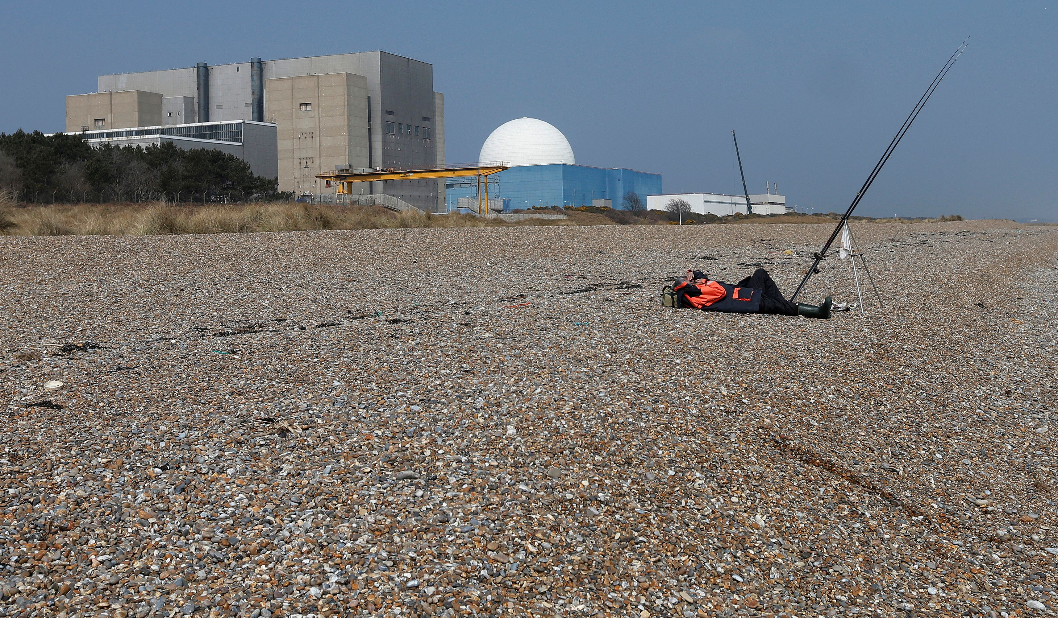 A fisherman takes a nap on Sizewell beach outside Sizewell nuclear power station in Suffolk, eastern England April 10, 2013. REUTERS/Suzanne Plunkett