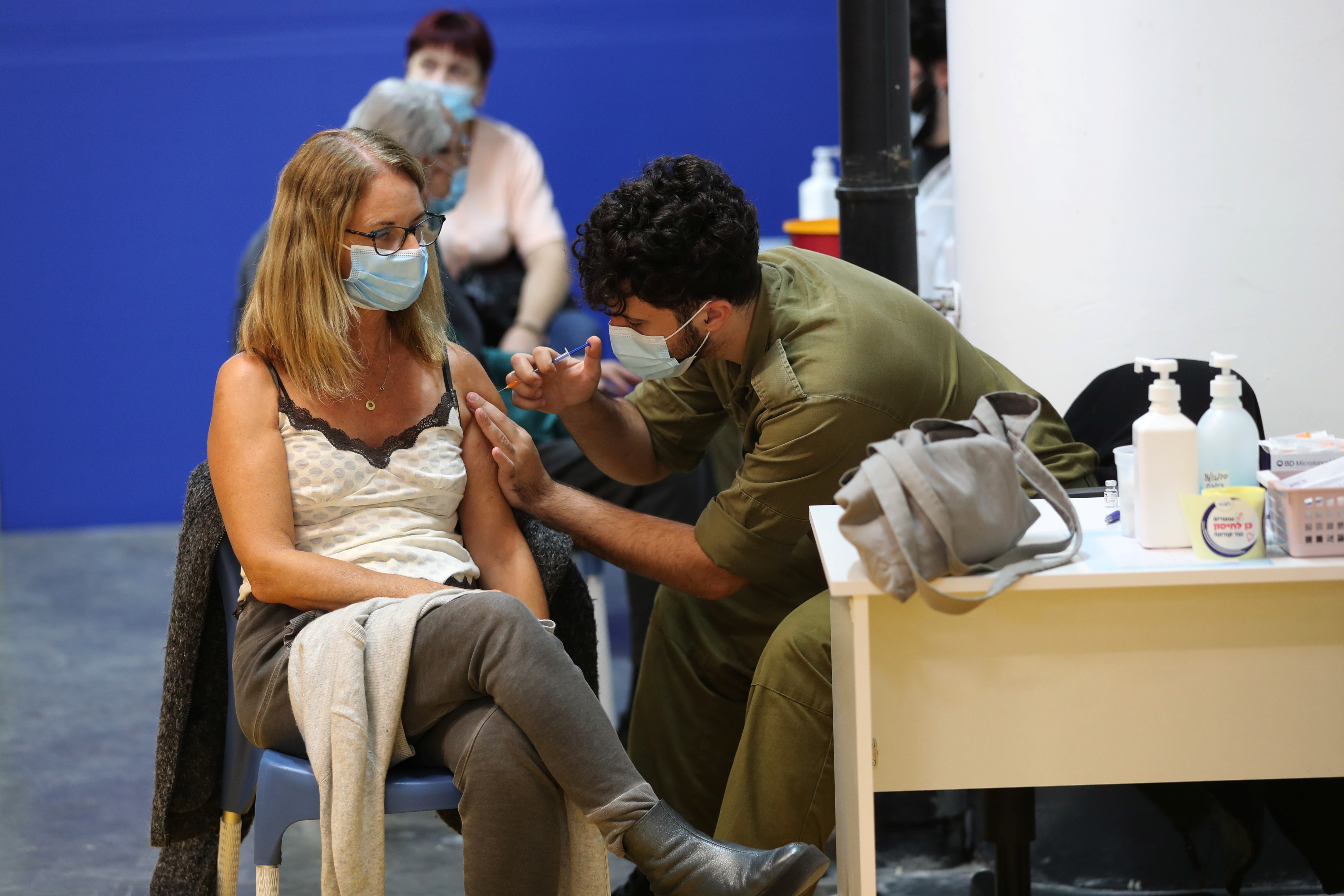 A woman receives a vaccination against the coronavirus disease (COVID-19) at a temporary healthcare maintenance organisation (HMO) centre amid Israel