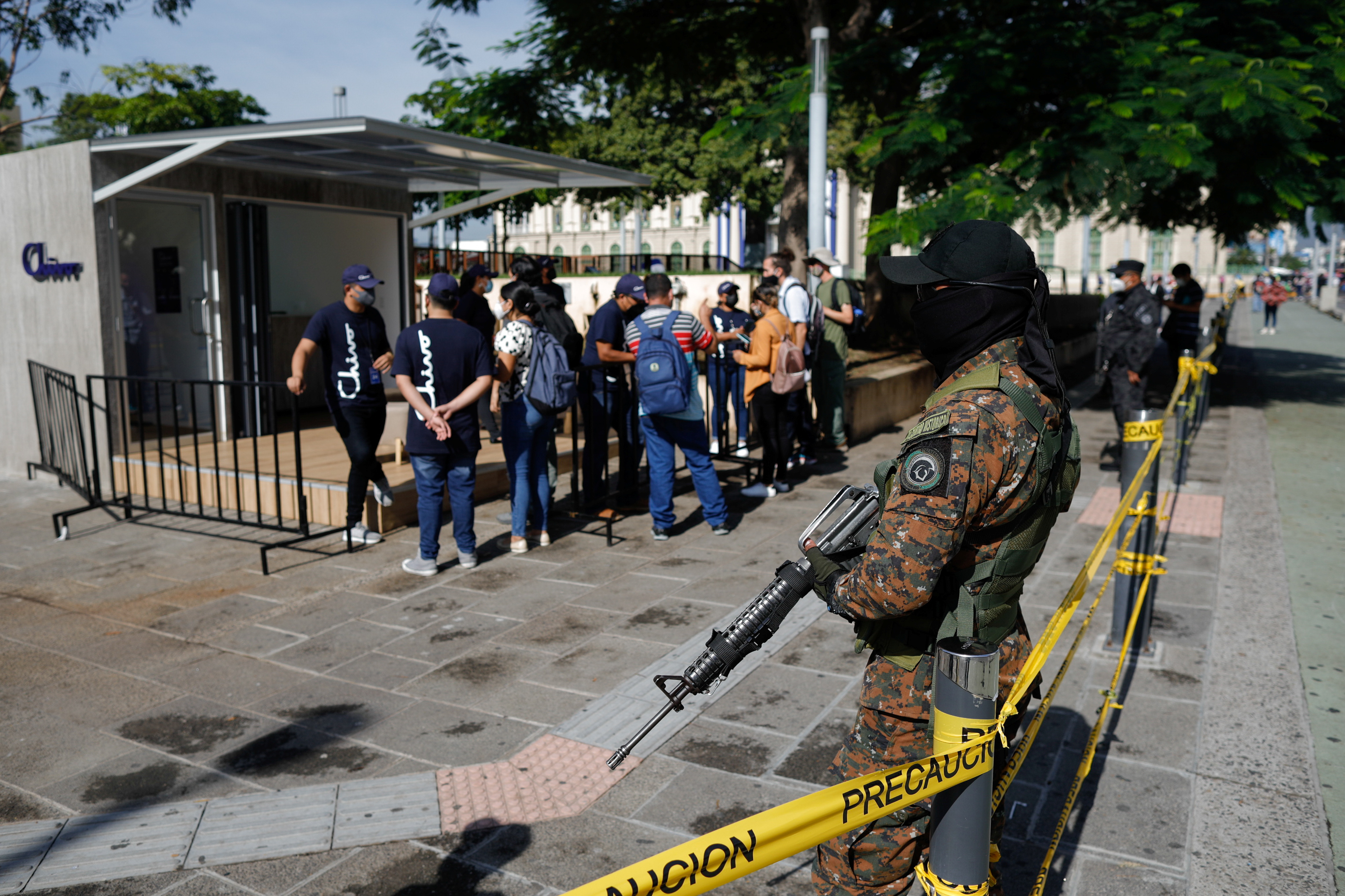 A soldier stands guard while people ask for information about the use of Bitcoin, outside an ATM of Chivo wallet, a Bitcoin wallet that Salvadoran government is launching for the use of Bitcoin as a legal tender, in San Salvador, El Salvador, September 7, 2021. REUTERS/Jose Cabezas
