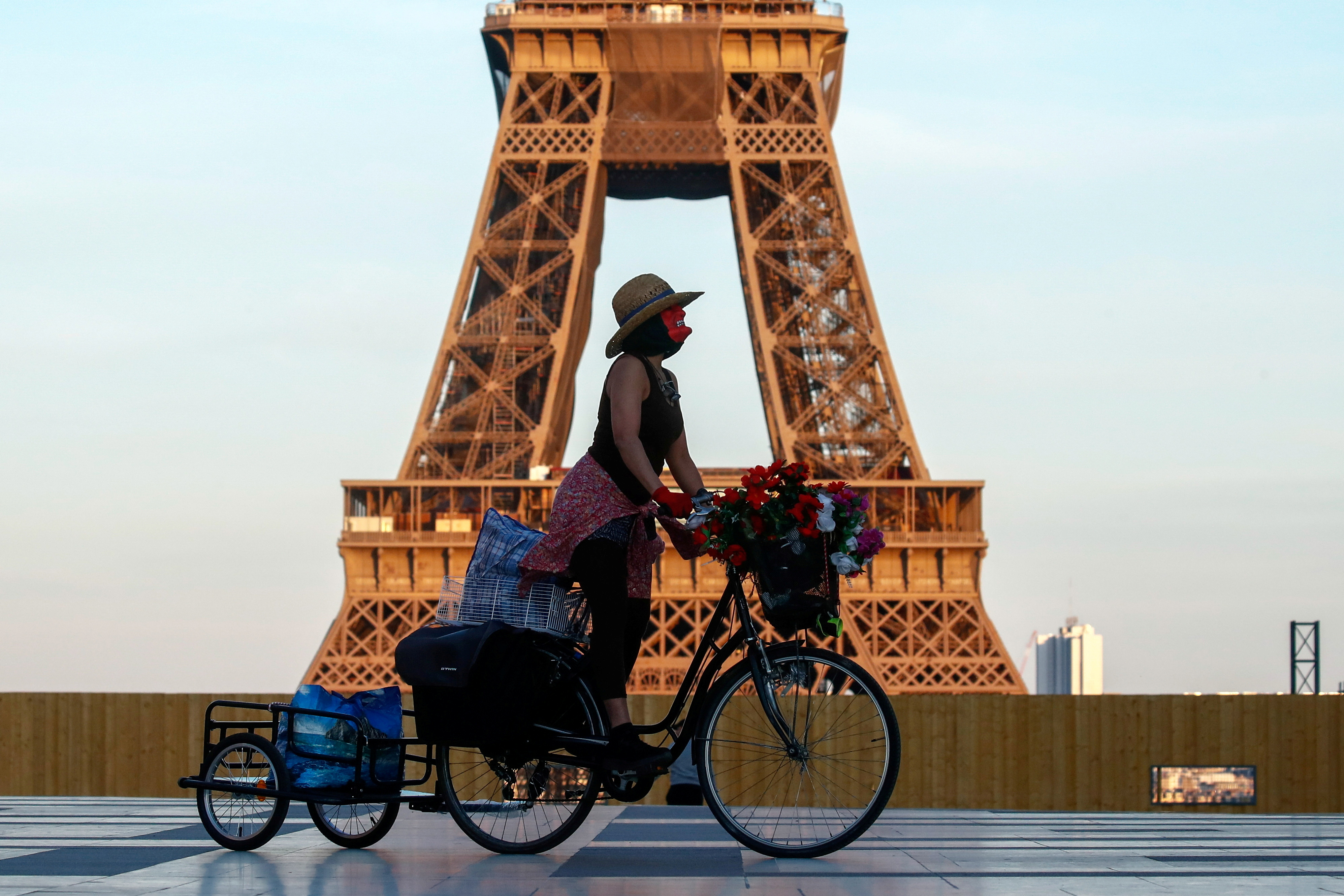 A woman, wearing a mask, rides her bicycle near the Eiffel tower at Trocadero square in Paris during the nationwide curfew, from 7 p.m to 6 a.m, due to tighter measures against the spread of coronavirus disease (COVID-19) in France, April 26, 2021. REUTERS/Gonzalo Fuentes/File Photo