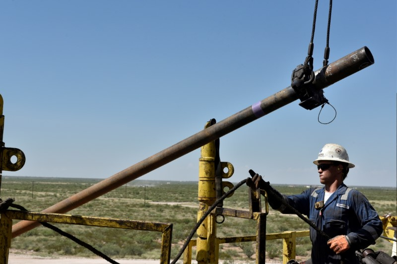 A drilling crew member raises drill pipe onto the drilling rig floor on an oil rig in the Permian Basin near Wink, Texas U.S. August 22, 2018. REUTERS/Nick Oxford