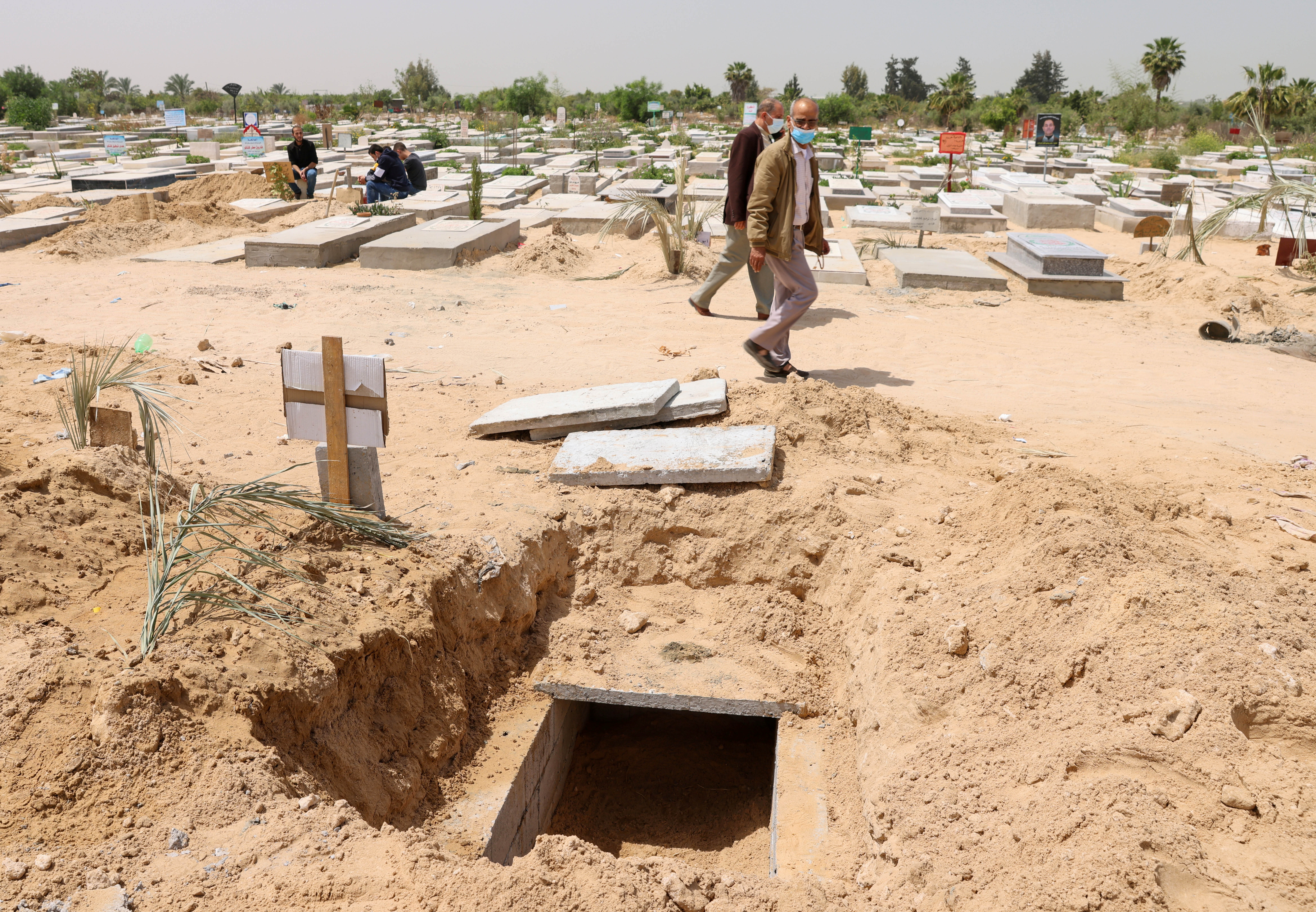 Palestinians walk past a grave dug for a coronavirus disease (COVID-19) victim, at a cemetery, east of Gaza City April 20, 2021. Picture taken April 20, 2021. REUTERS/Mohammed Salem