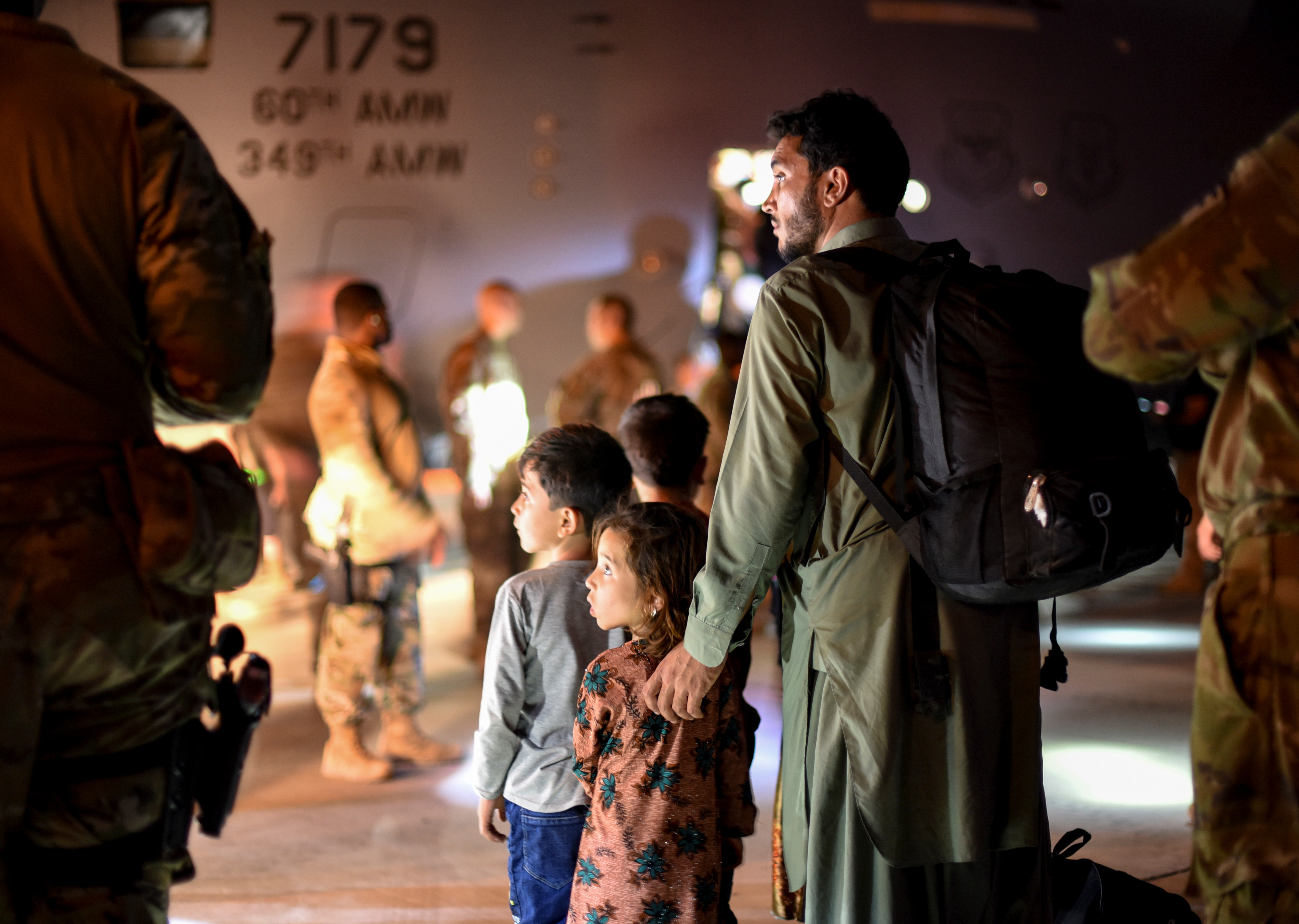 A father and children evacuees from Afghanistan leave a U.S. C-17 Globemaster transport plane after arriving at Ali Al Salem Air Base, Kuwait, August 24, 2021.  U.S. Air Force/Staff Sgt. Ryan Brooks/Handout via REUTERS.