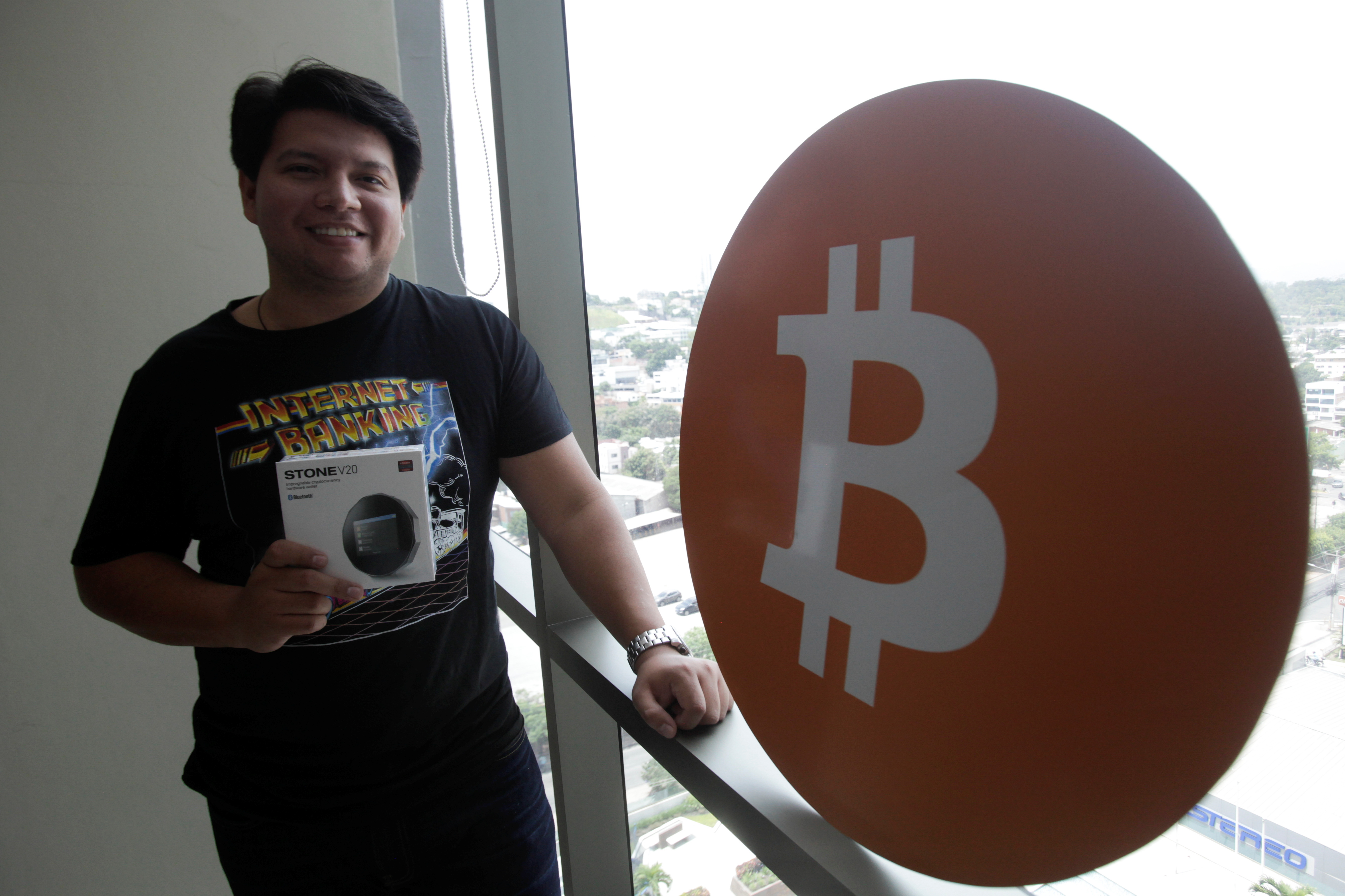 Juan Mayen, 28, chief executive of Honduran firm TGU Consulting Group, poses for a photo with a cryptocurrency hardware wallet at the TGU office where he installed the first cryptocurrency ATM machine in the country that allows users to acquire bitcoin and ethereum using the local lempira currency, in Tegucigalpa, Honduras August 27, 2021. REUTERS/Fredy Rodriguez