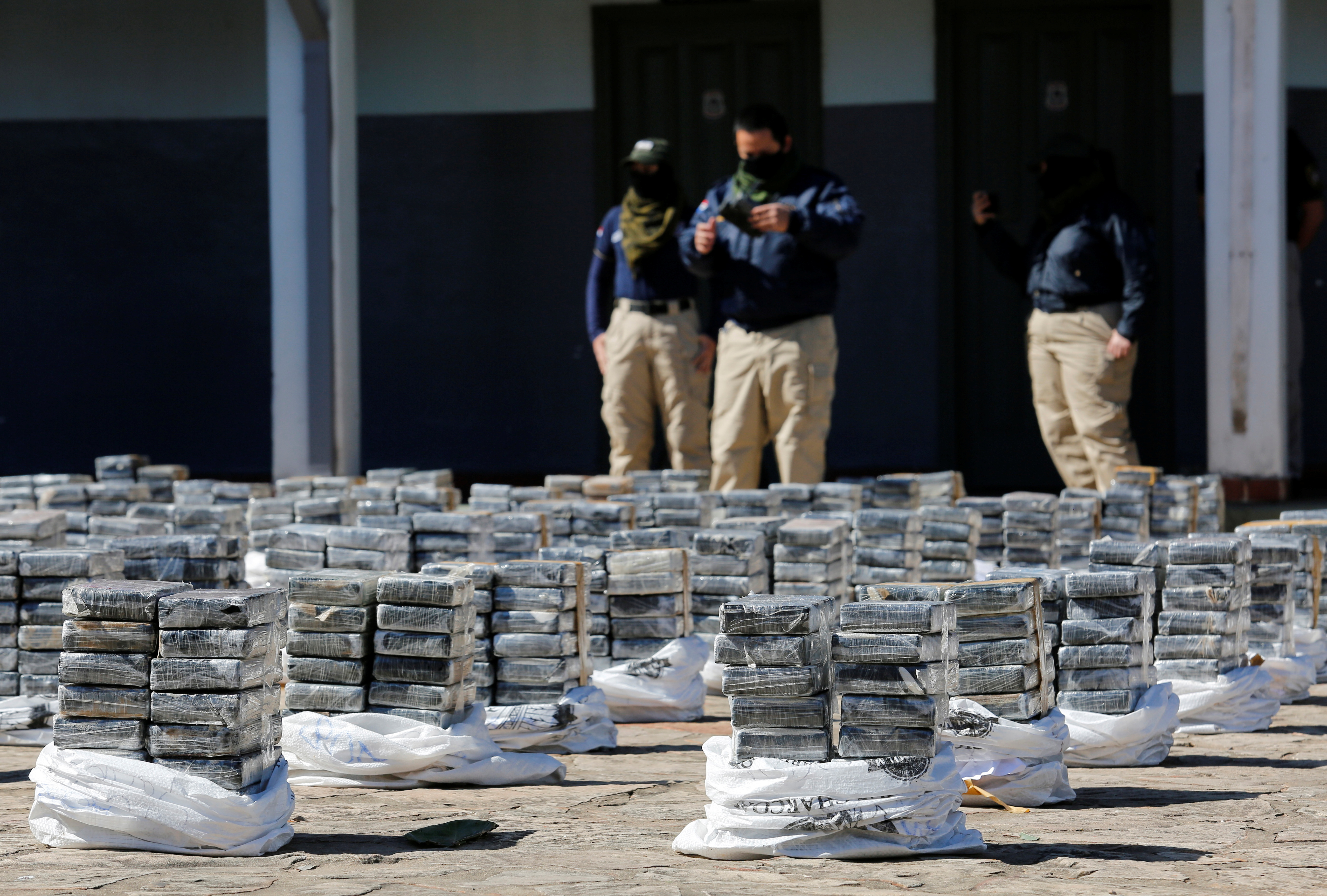 Paraguayan police put on display packages containing cocaine, which were found in a warehouse ready to be shipped abroad along with a load of organic sugar, according to authorities, in Asuncion, Paraguay July 28, 2021. REUTERS/Cesar Olmedo