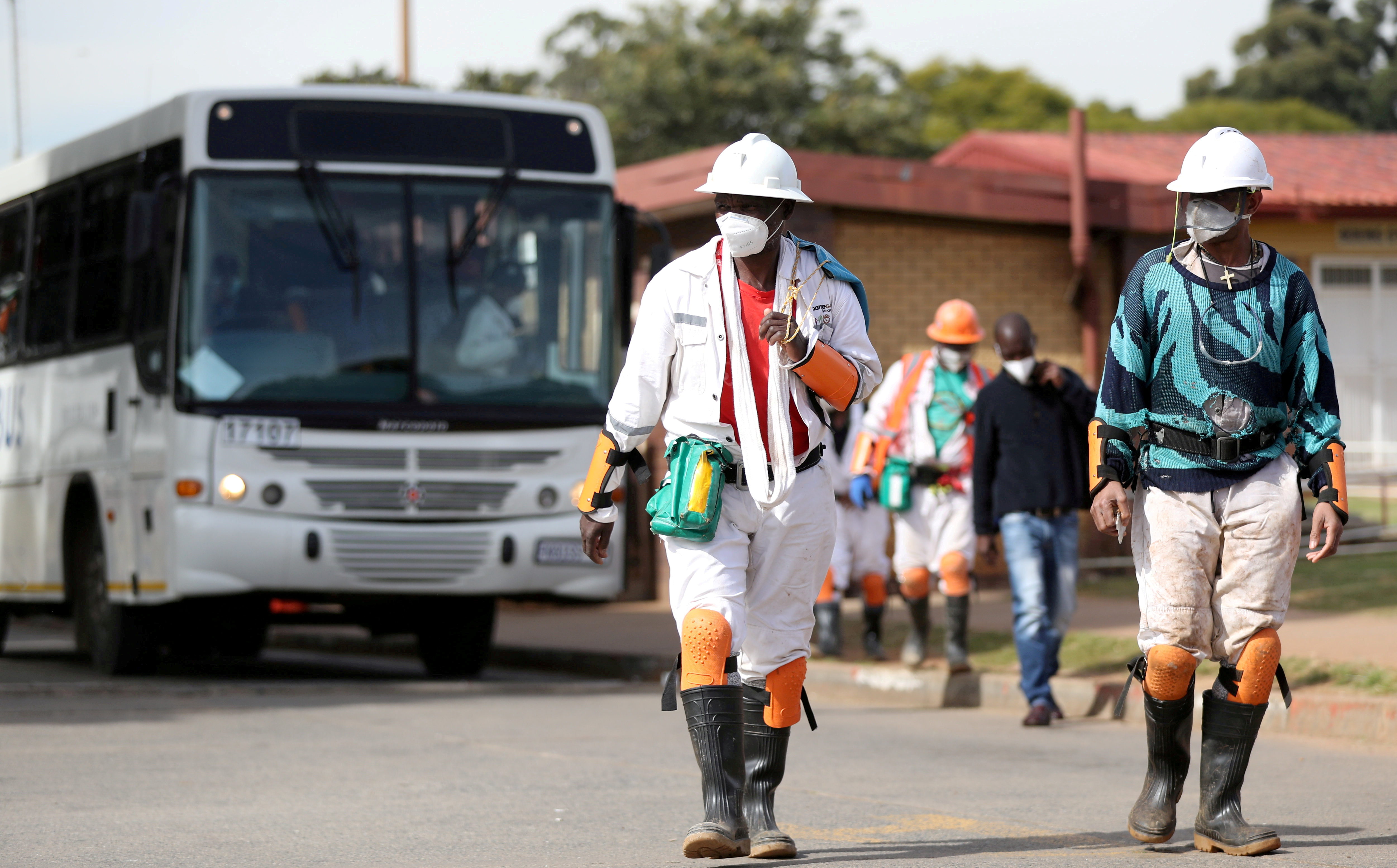 Mine workers wearing face masks arrive ahead of their shift, amid a nationwide coronavirus disease (COVID-19) lockdown, at a mine of Sibanye-Stillwater company in Carletonville, South Africa, May 19, 2020. REUTERS/Siphiwe Sibeko
