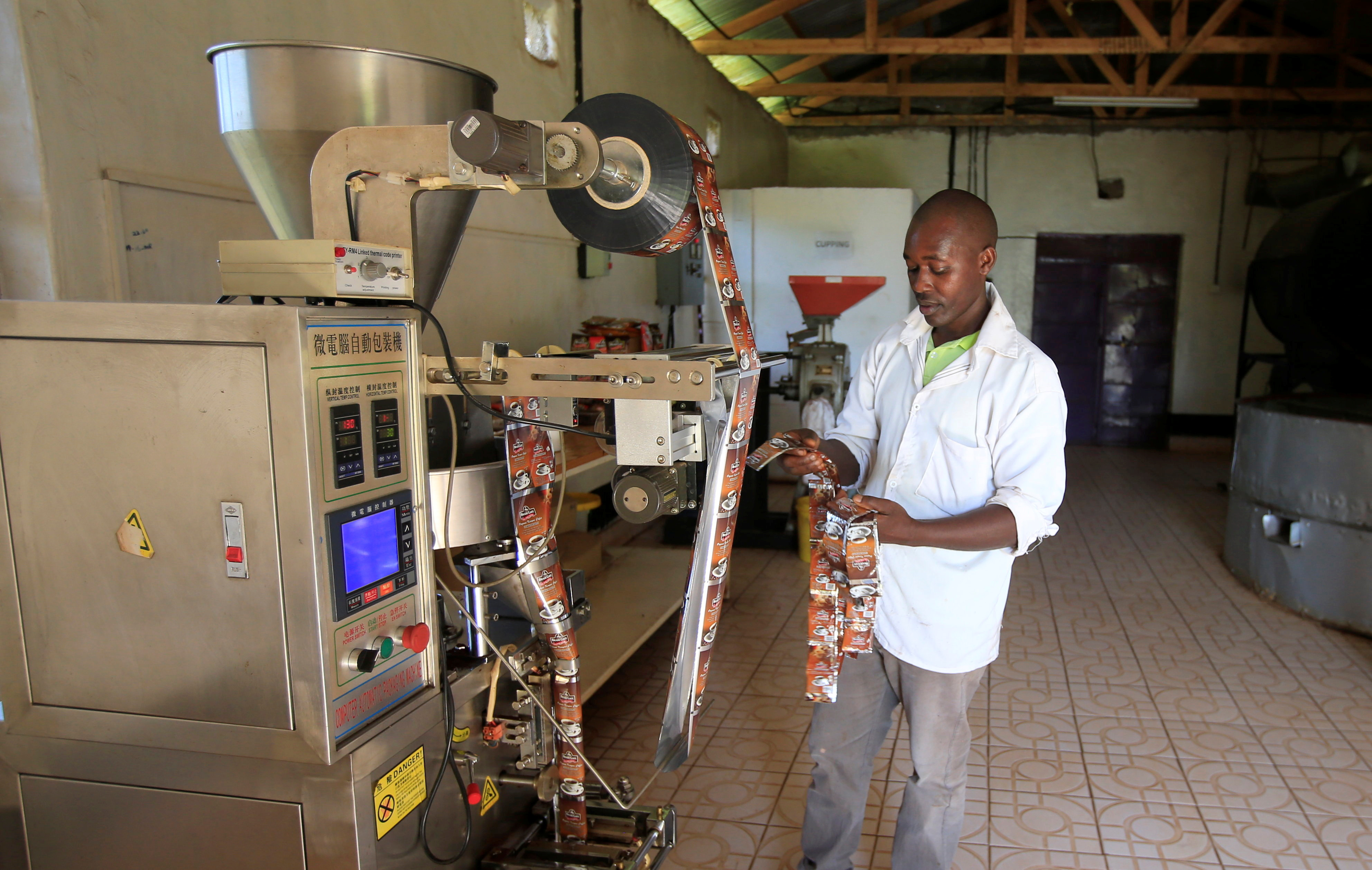 Bradegate coffee factory manager Ephraim Maina sorts coffee sachets after sealing at the factory in Karatina near Nyeri town, Kenya June 3, 2021. REUTERS/Monicah Mwangi