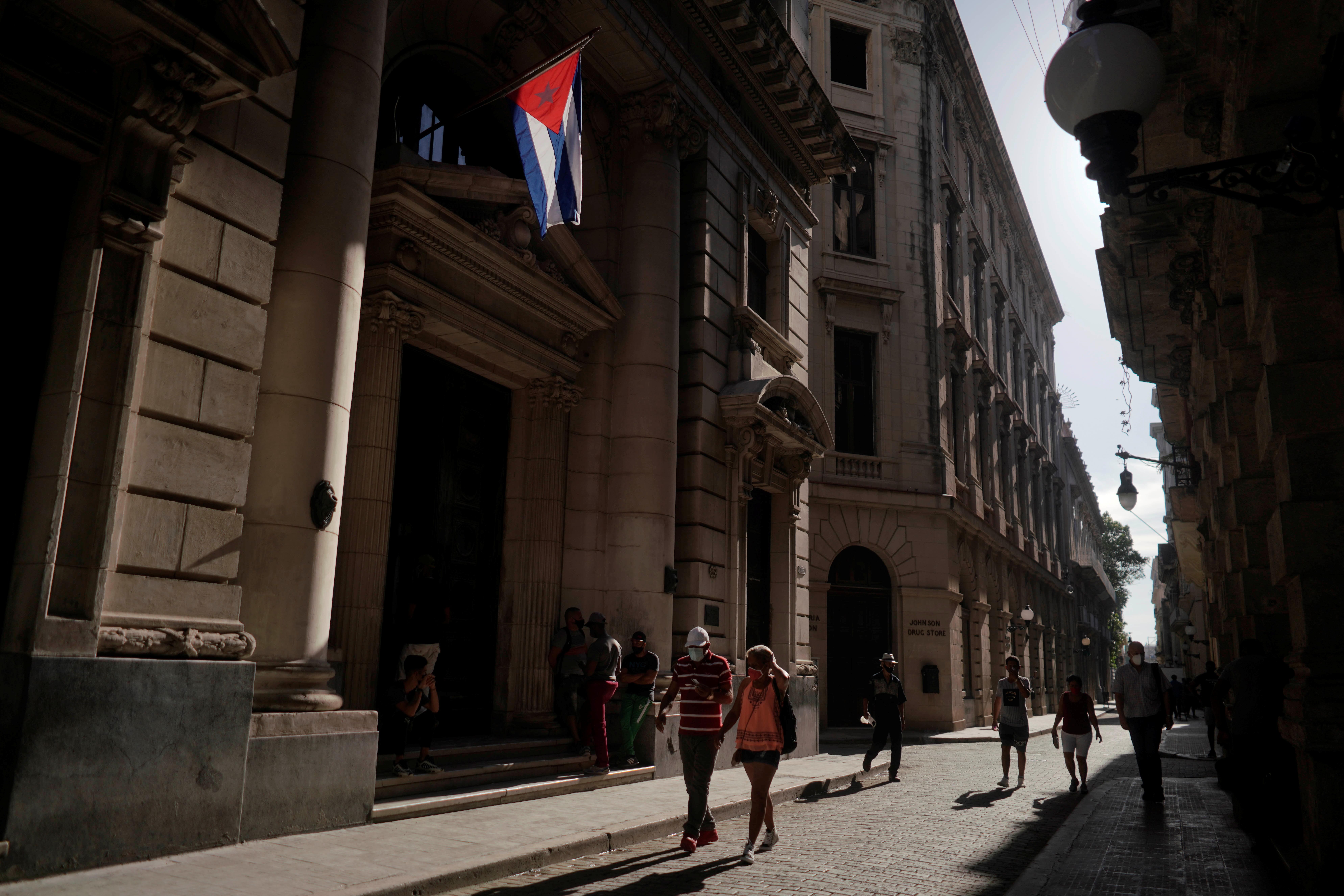 People pass under a Cuban flag in Havana, Cuba, July 13, 2021. REUTERS/Alexandre Meneghini