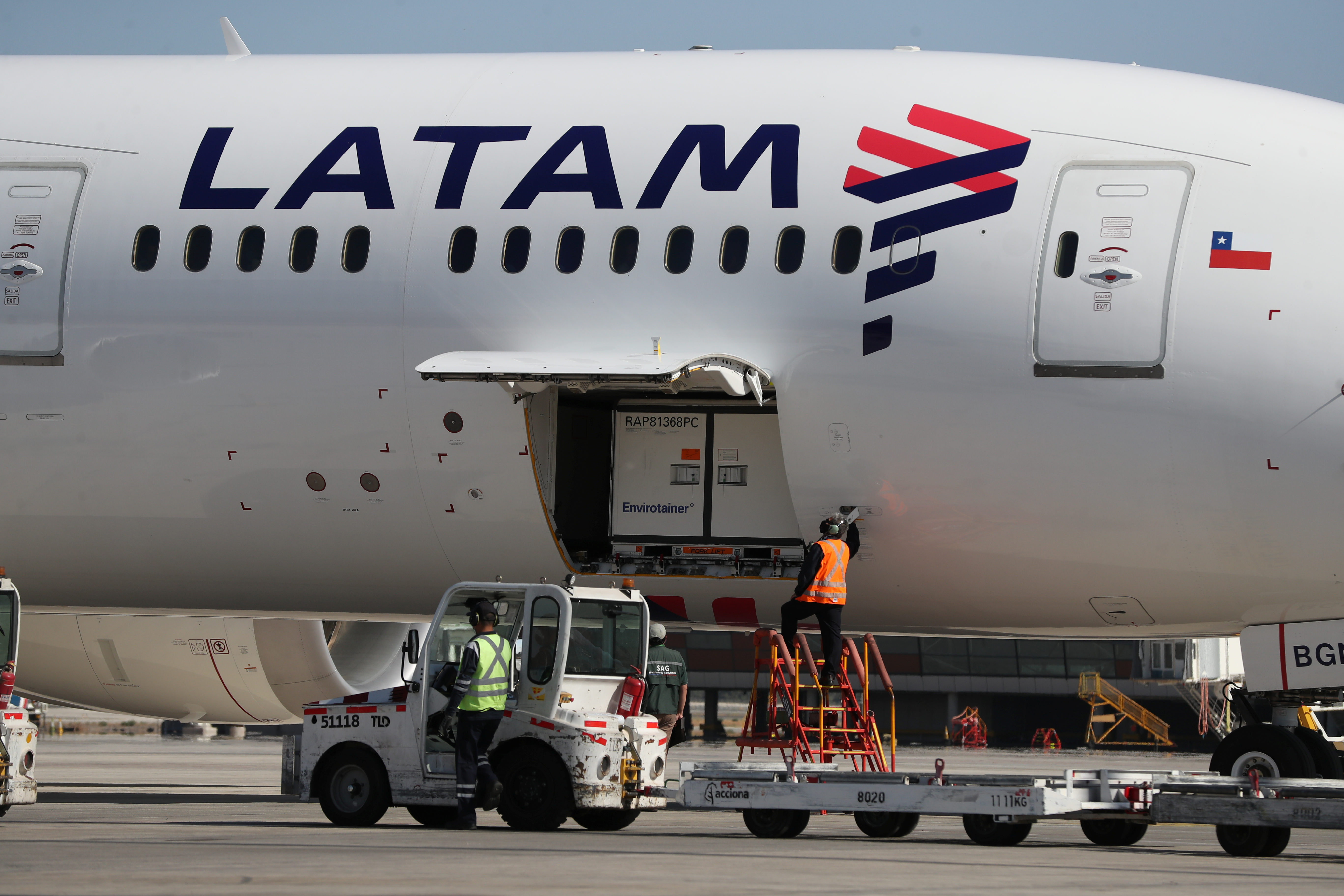 Workers unload containers transporting a batch of the Sinovac coronavirus disease (COVID-19) vaccine at the international airport of Santiago, Chile, January 28, 2021. Picture taken January 28, 2021. REUTERS/Ivan Alvarado