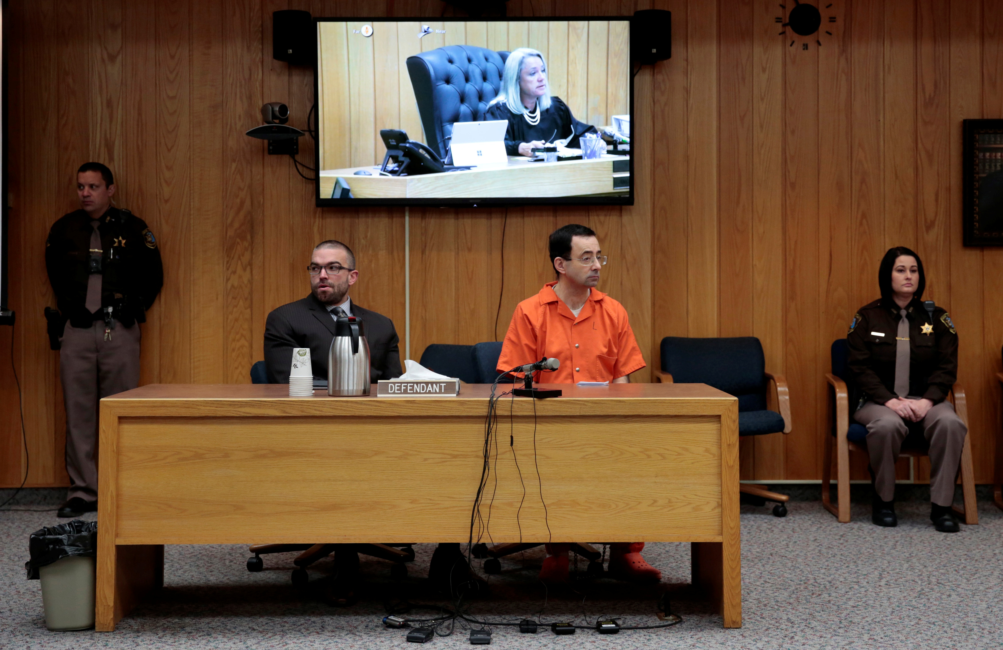 Larry Nassar, a former team USA Gymnastics doctor who pleaded guilty in November 2017 to sexual assault charges, and his defense attorney Matt Newburg listen to Judge Janice Cunningham during Nassar's sentencing hearing in the Eaton County Court in Charlotte, Michigan, U.S., February 5, 2018. REUTERS/Rebecca Cook