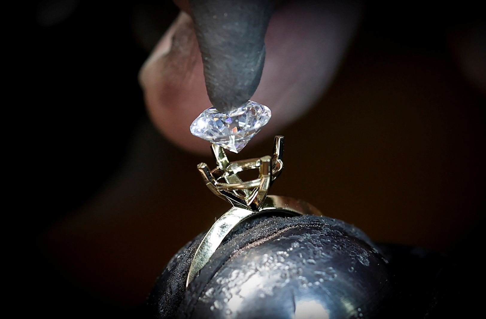 A worker sets an Aether diamond made from captured CO2 into a ring at the RFG Manufacturing Riviera jewelry design facility in Manhattan in New York City, New York, U.S., September 30, 2021. Picture taken September 30, 2021.  REUTERS Mike Segar