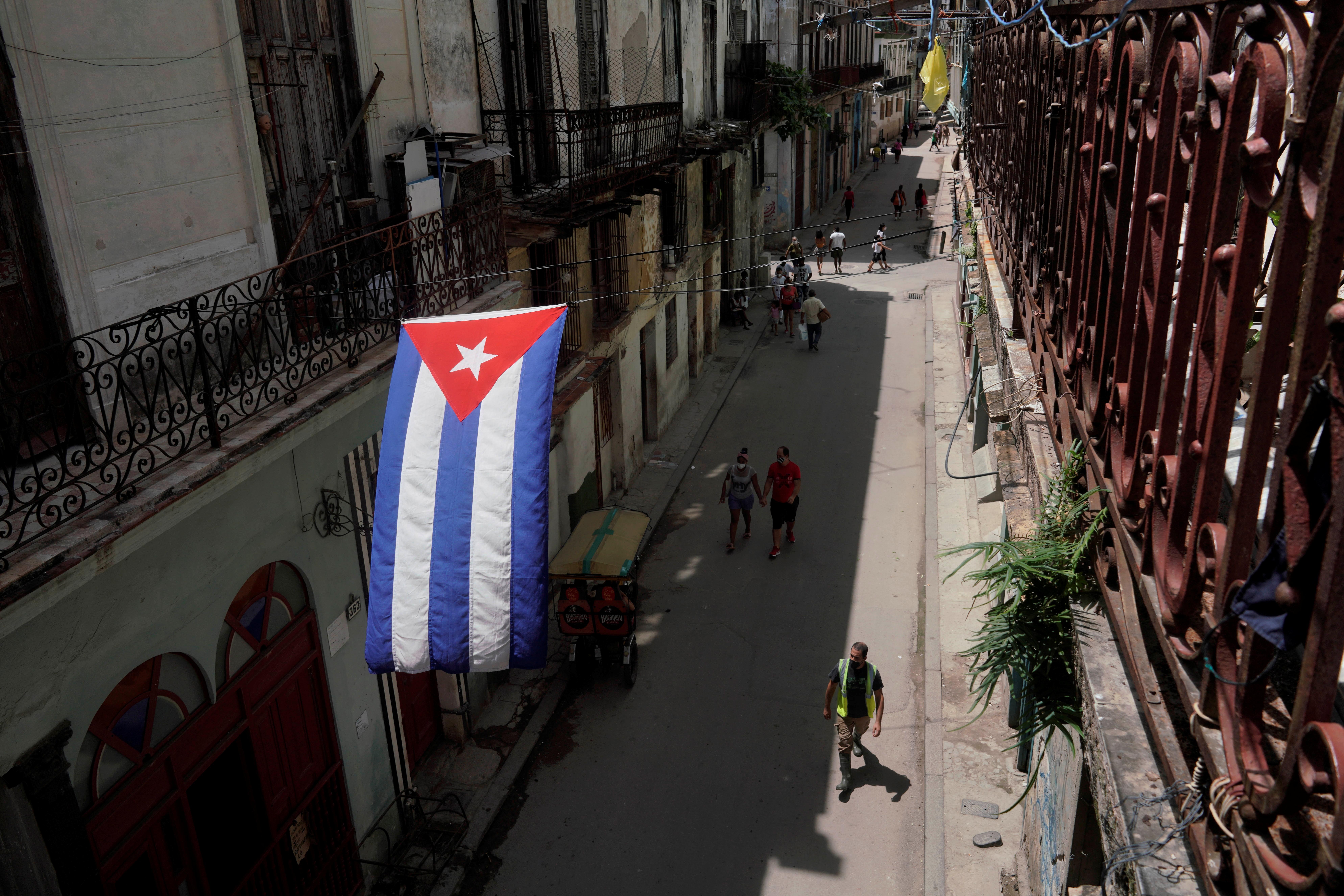 A Cuban flag hangs over a street in downtown Havana, Cuba, July 15, 2021. REUTERS/Alexandre Meneghini