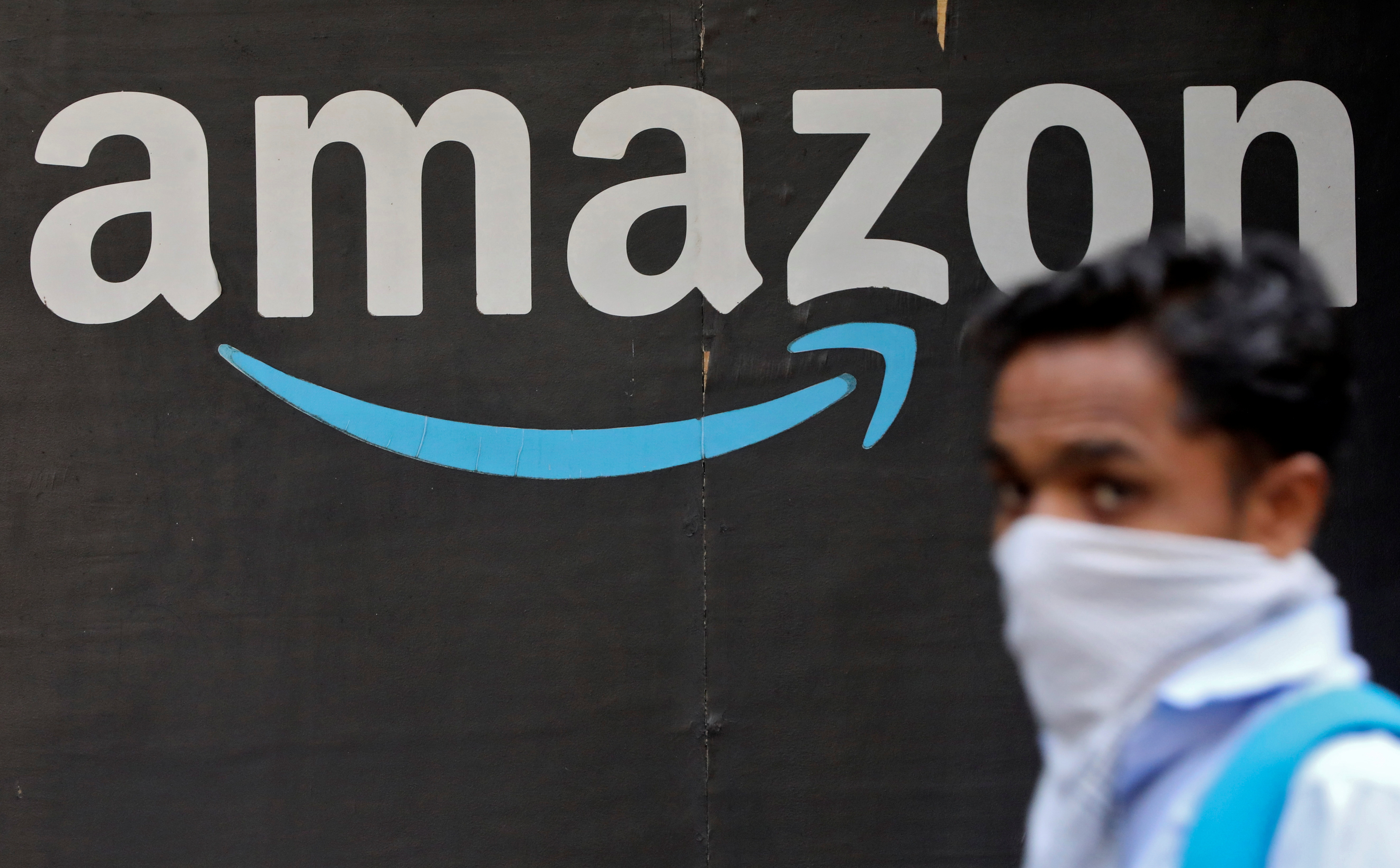 A man walks past an Amazon logo outside the company's collection point in Mumbai, India, March 19, 2021. REUTERS/Francis Mascarenhas