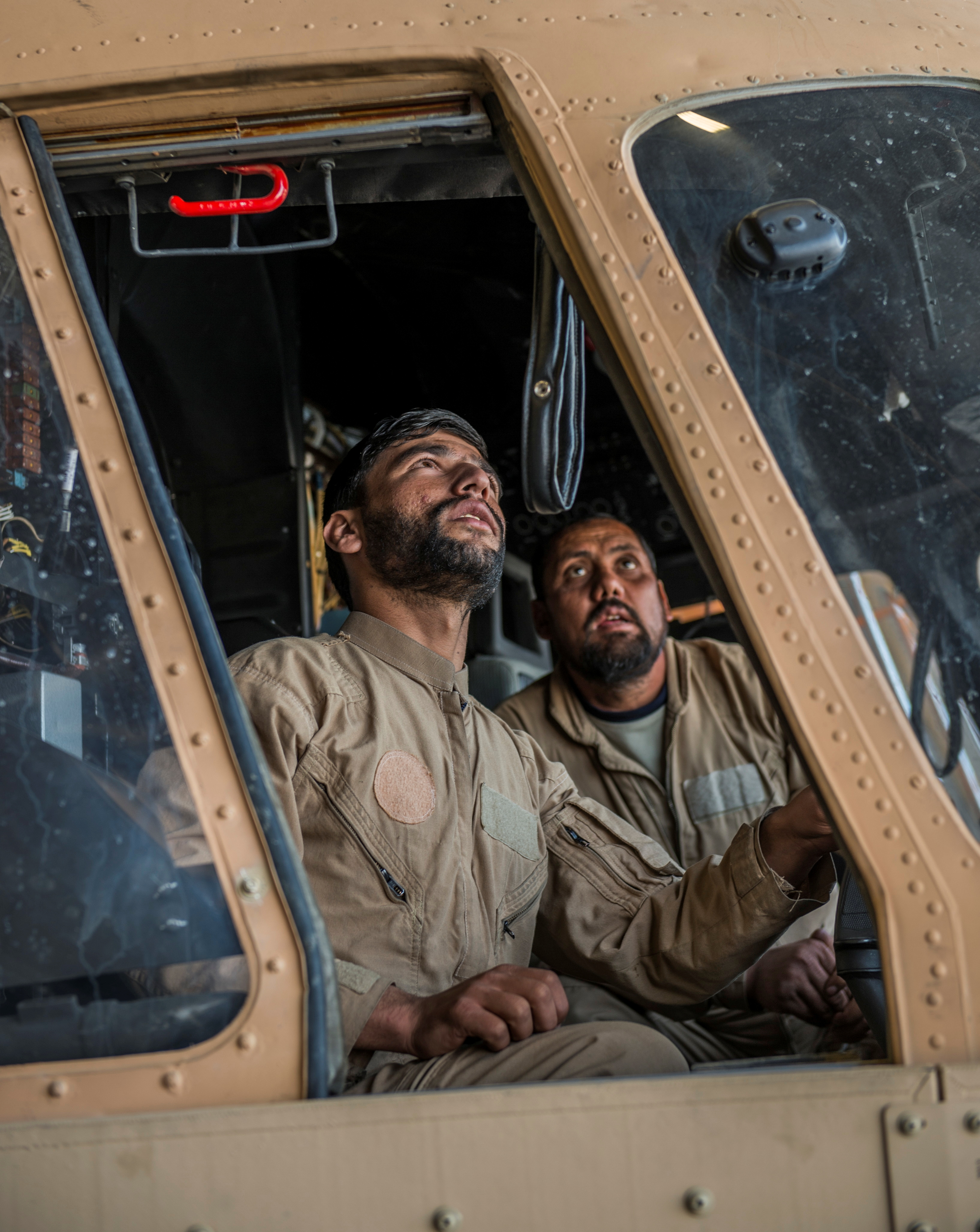 Afghanistan Air Force member Khalid and Sergeant Hyatullah of the Kandahar Air Wing work in the cockpit of an MI-17 helicopter on Kandahar Airfield, Afghanistan, November 2, 2017. Picture taken November 2, 2017. To match Special Report USA-AFGHANISTAN/PILOTS    U.S. Air Force/Staff Sgt. Sean Martin/Handout via REUTERS